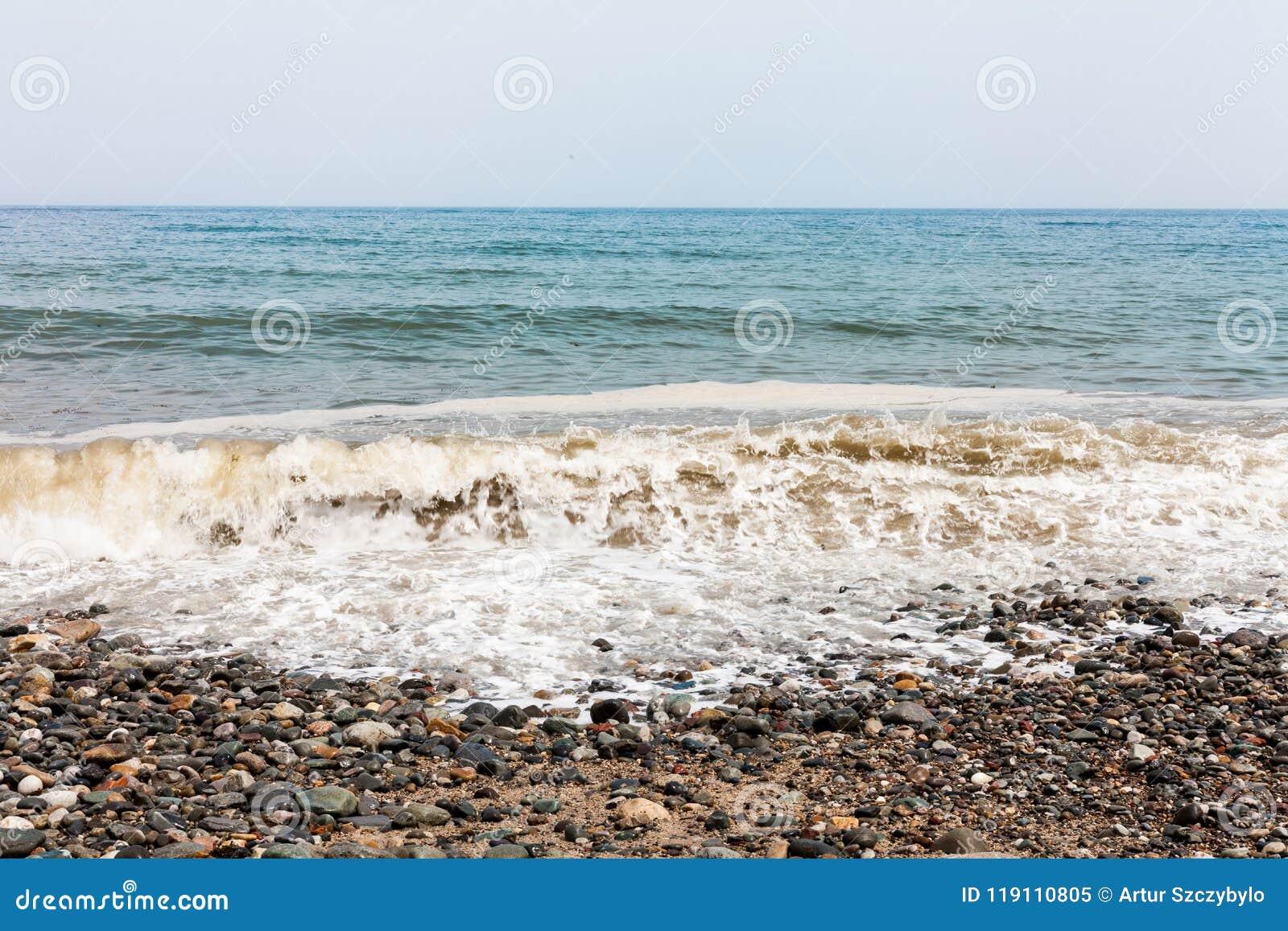 Dia nebuloso no lado da praia com as ondas que batem o litoral Espuma do mar nas ondas Praia rochosa com pedras coloridas Withou