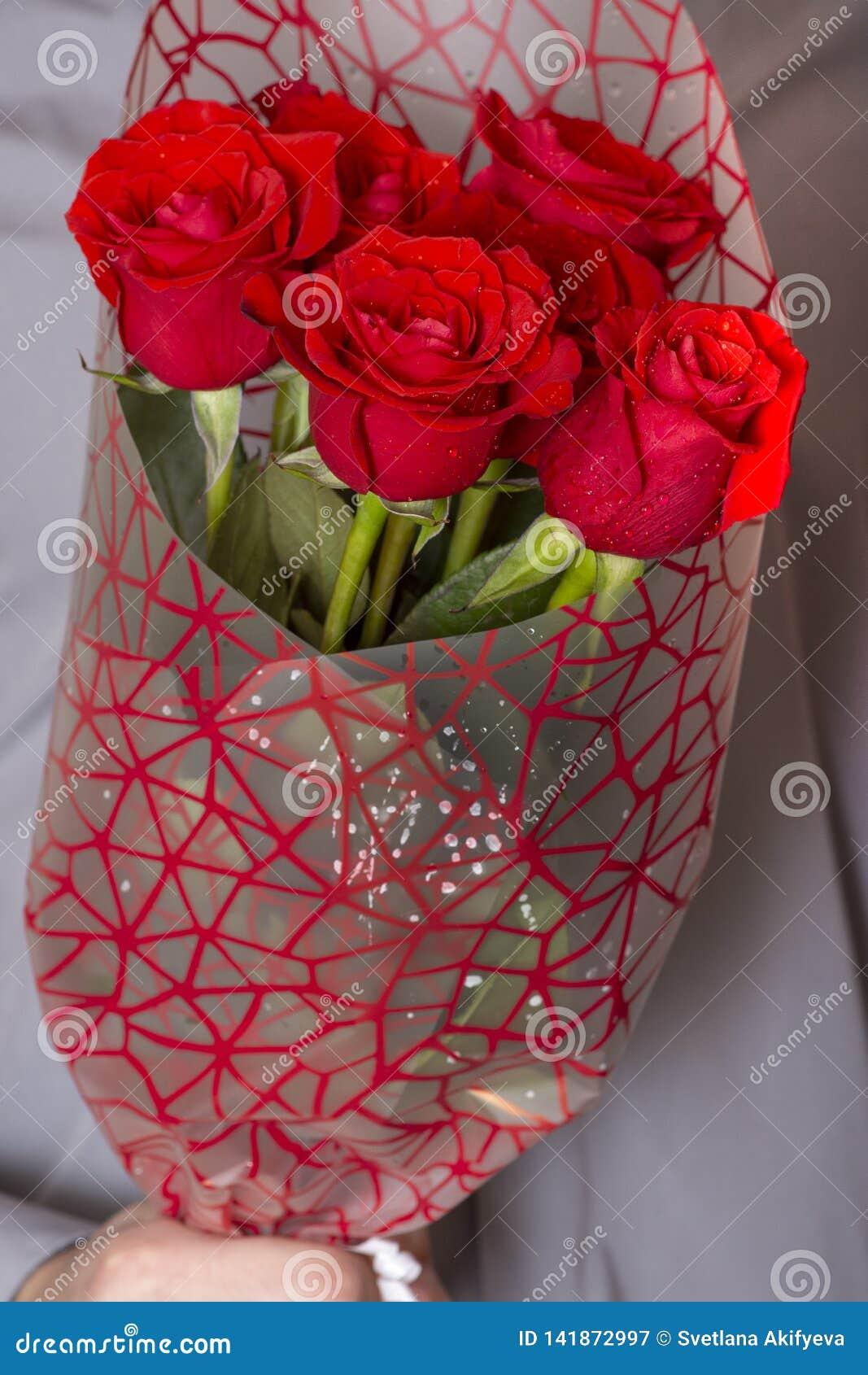 Dia ou proposta de Valentim Homem considerável feliz novo que guarda o grupo grande de rosas vermelhas em sua mão no fundo cinzen