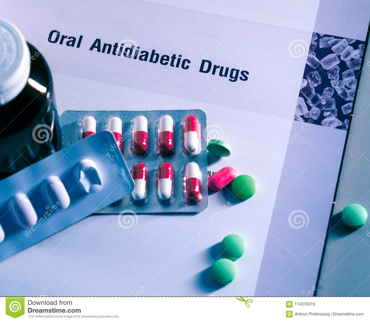 Diabetes drugs in packs and and medicine bottle placed on textbook. Green tablets and pink-white capsule pills. Diabetes mellitus