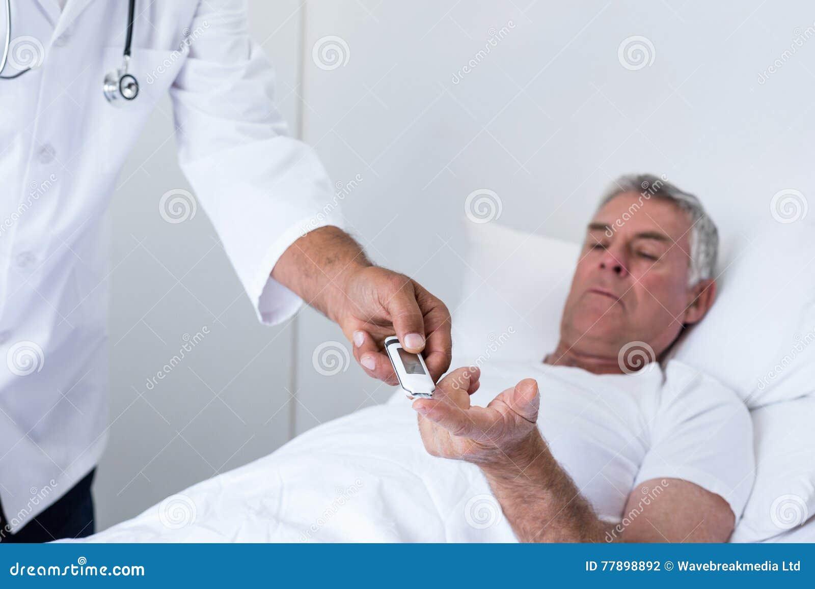 Diabetes masculino dos testes do doutor do homem superior no medidor da glicose