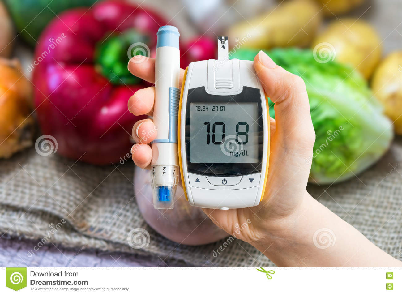 Diabetic diet and diabetes concept. Hand holds glucometer.