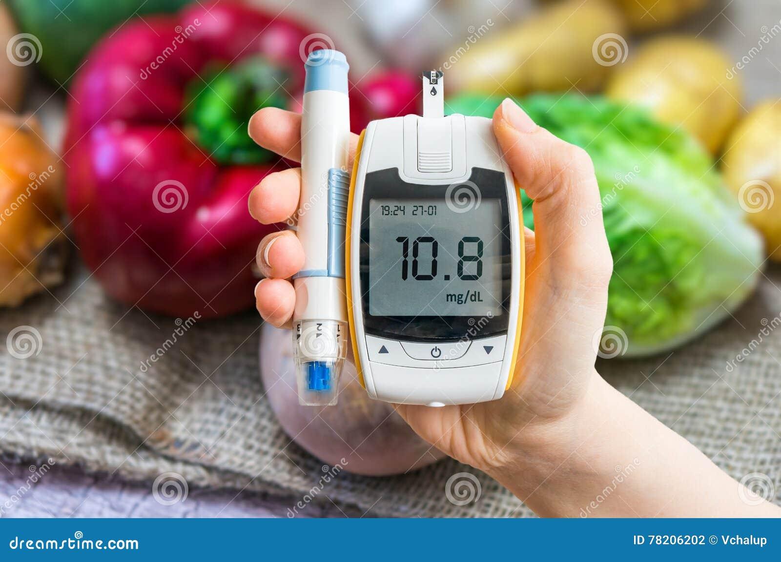 Diabetiskt banta och sockersjukabegreppet Handen rymmer glucometer