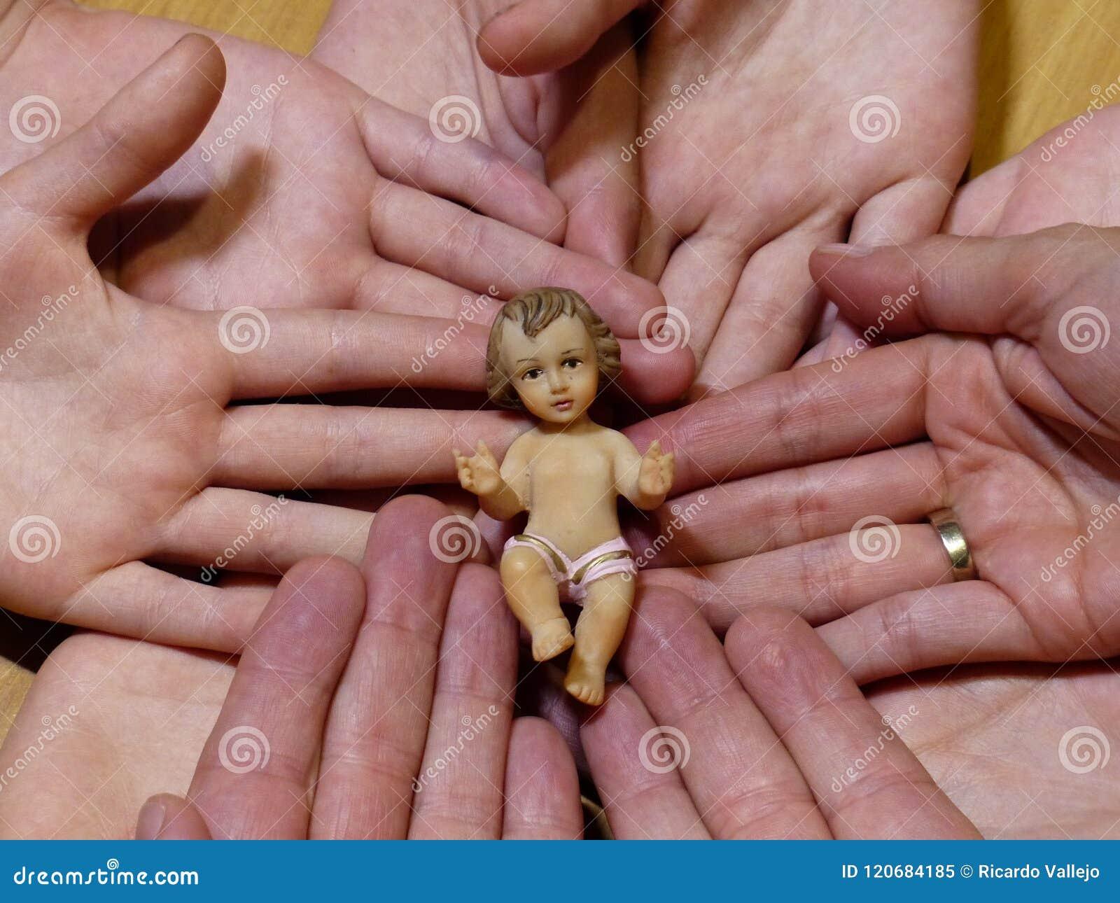 Diagramet av behandla som ett barn jesus liyng på händer av en familj och en vigselring