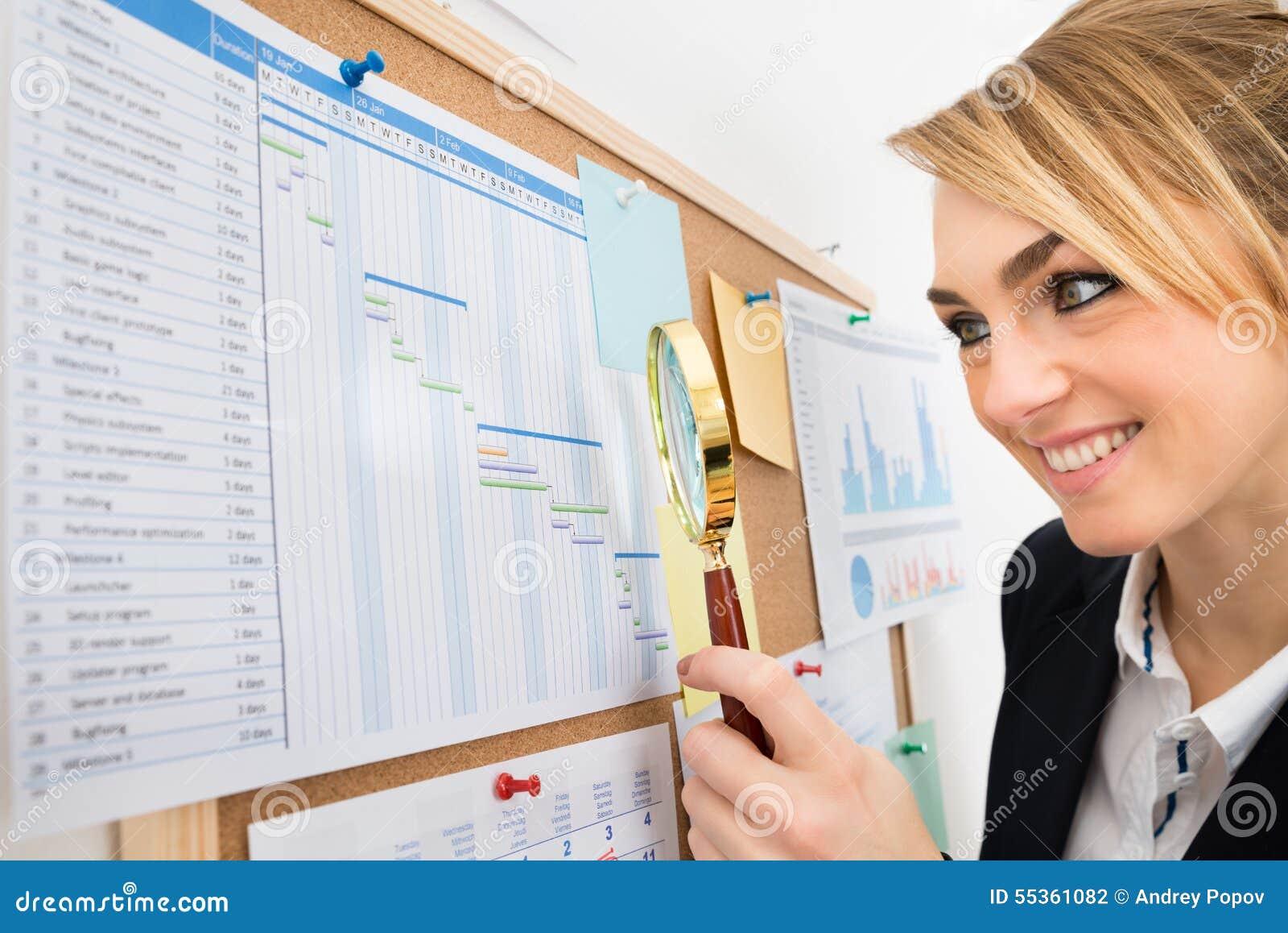 Diagramma di Gantt d esame della donna di affari con la lente d ingrandimento