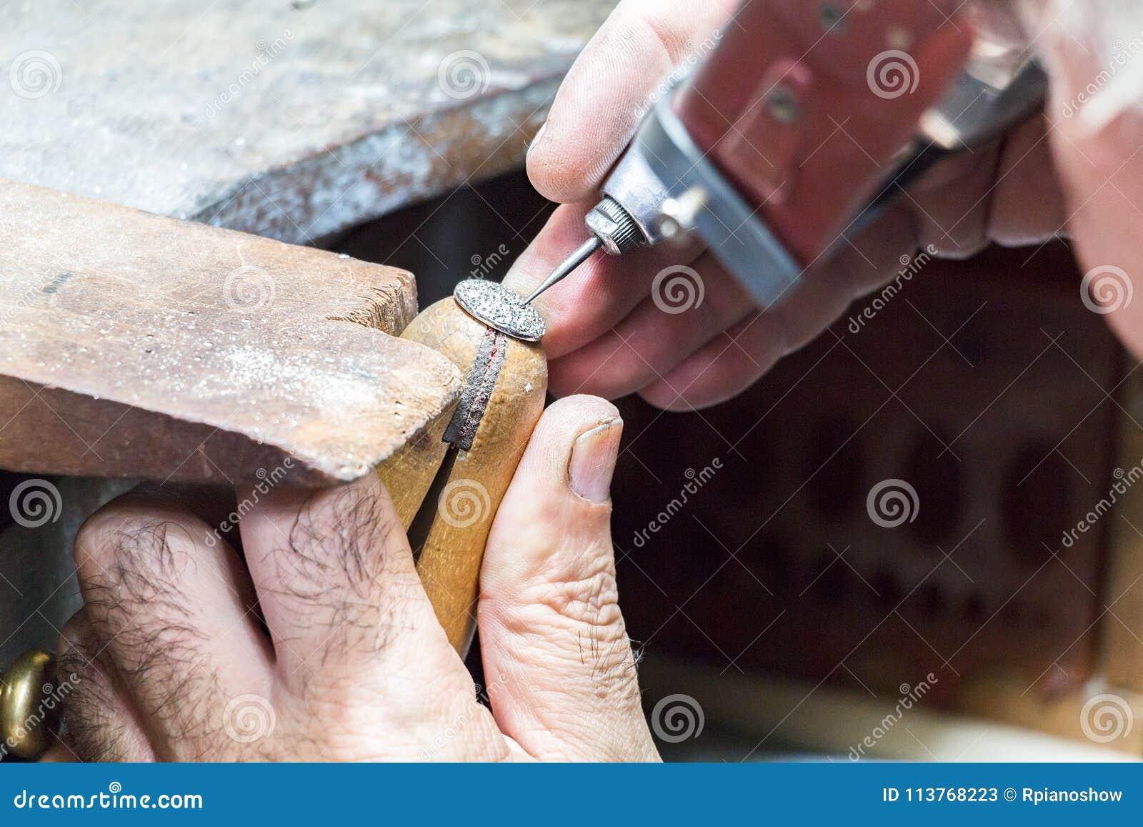 0abd0fd4eb8c Un joyero que lleva una lupa principal del visera está grabando diamantes en  un anillo puesto en una abrazadera de madera usando los ejes de una flexión