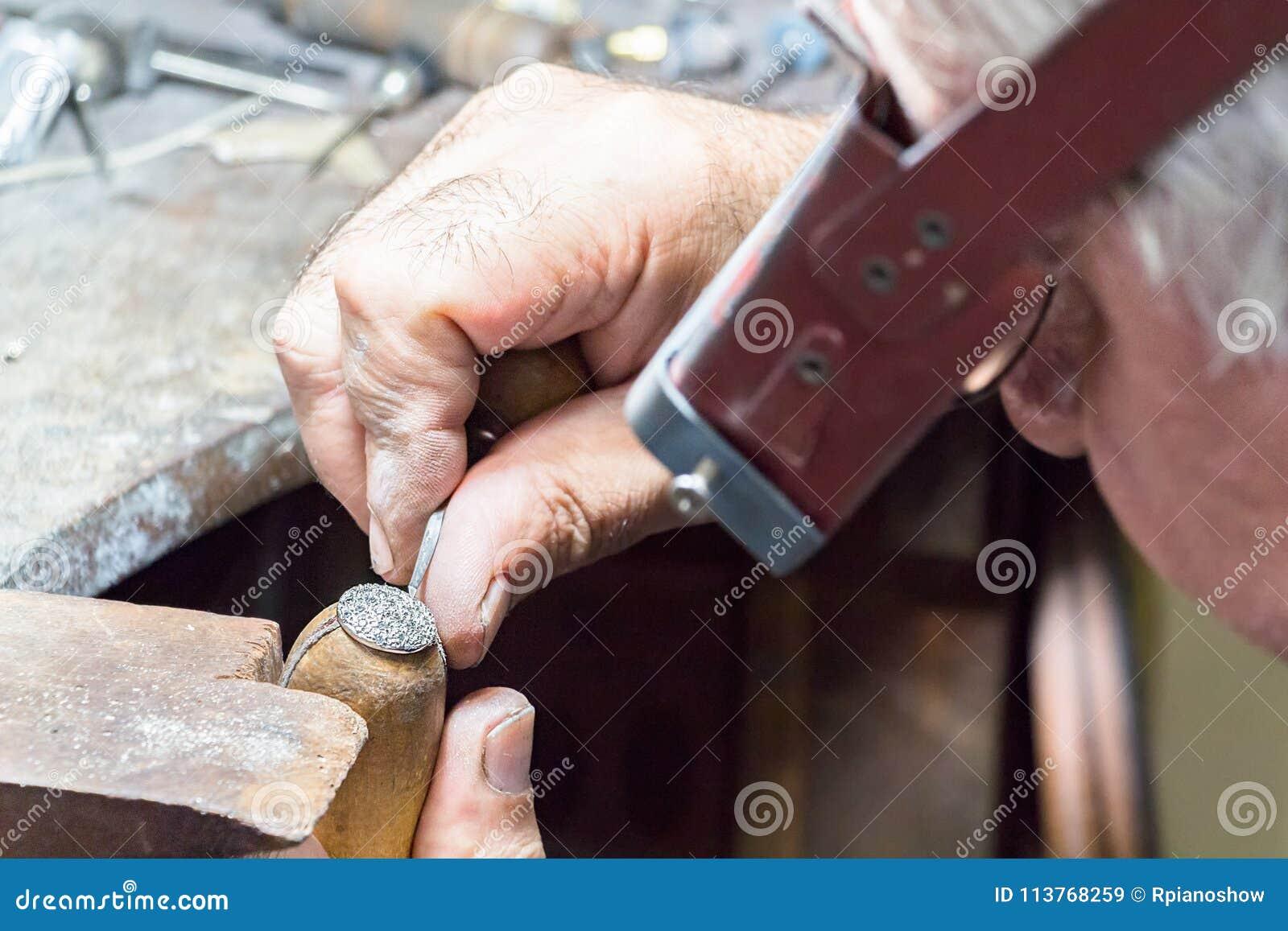 fa459ef23e2a Un joyero que lleva una lupa principal del visera está grabando diamantes en  un anillo puesto en una abrazadera de madera con un buril manual
