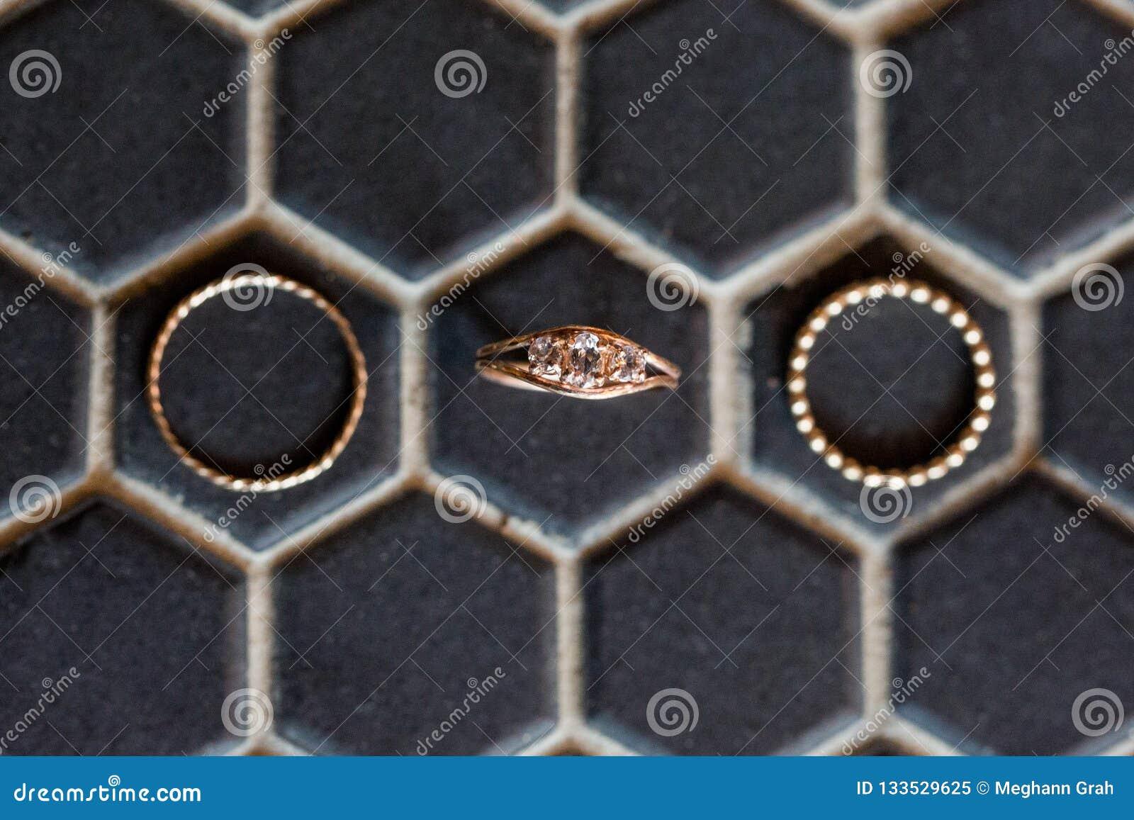 Diamentowy pierścionek zaręczynowy i ślubni zespoły na czarnym sześciokąta tle