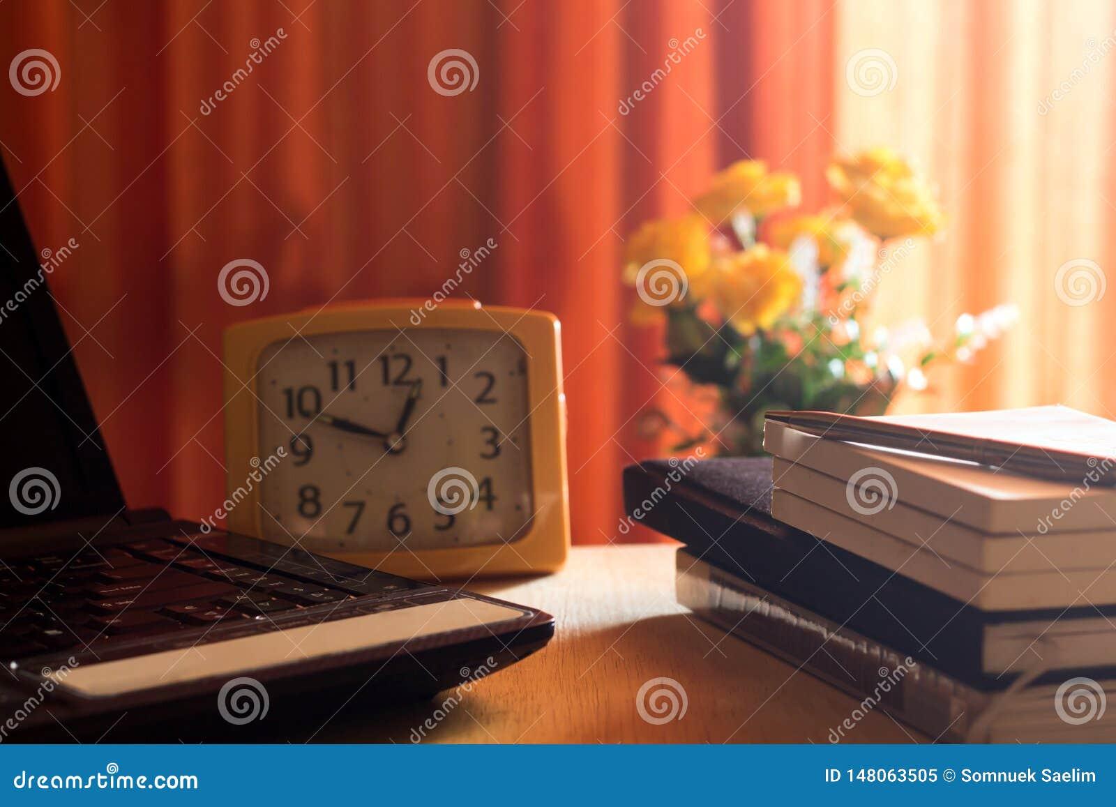 Diario e labtop per lavoro sulla tavola di legno con il fiore e la tenda rossa, taccuino, libro, penna, diario, orologio e sullo