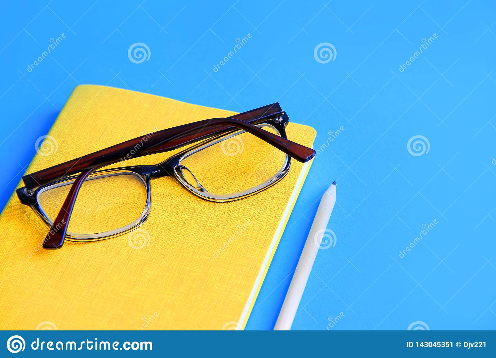 diary on it are glasses next to a pencil on a blue background