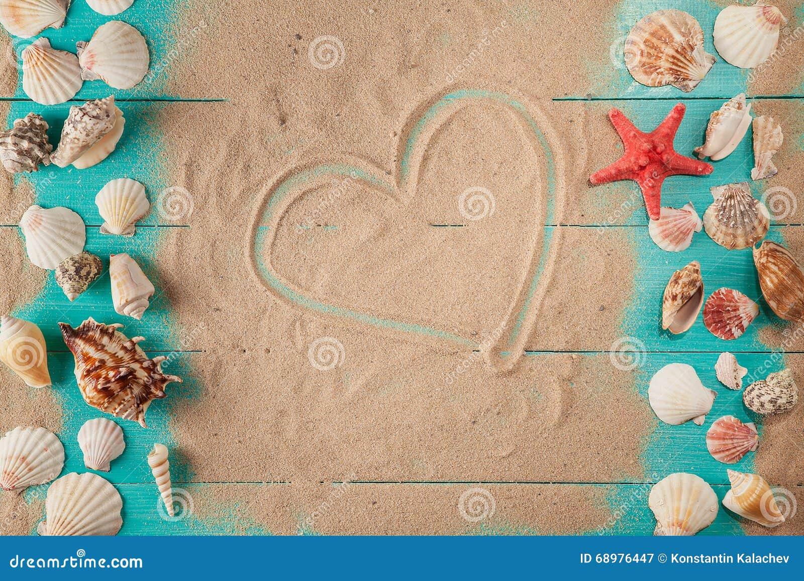 Dibujo del corazón en la arena entre conchas marinas