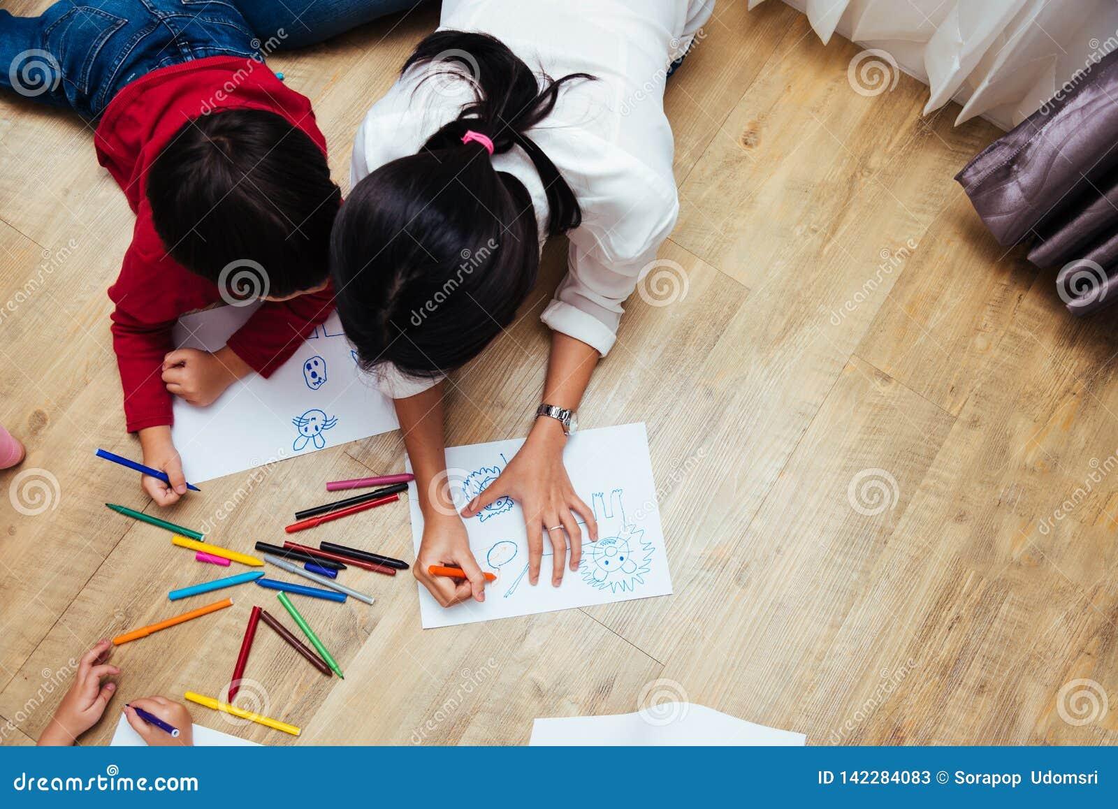 Dibujo feliz de la pintura de la guardería del muchacho y de la muchacha del niño del grupo de los niños de la familia de la visi