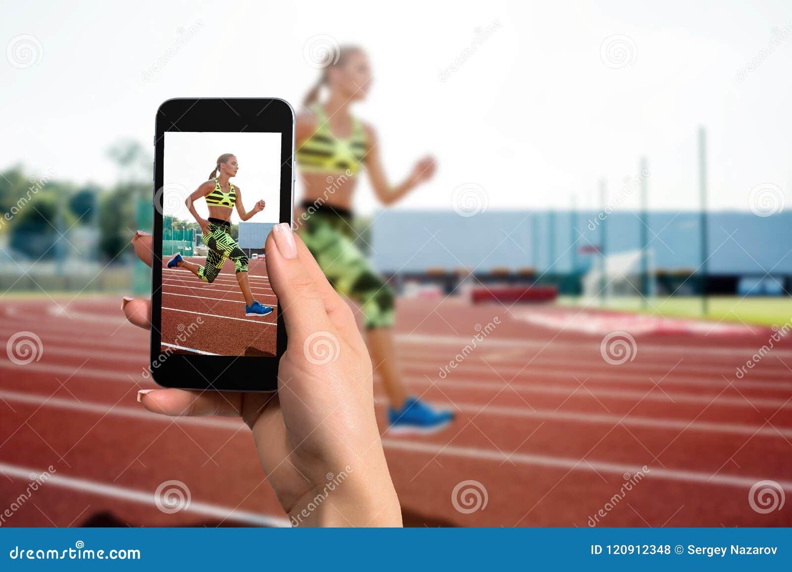 Dicht beeld die van vrouwelijke handen mobiele telefoon met de wijze van de fotocamera op het scherm houden Bebouwd beeld van lop