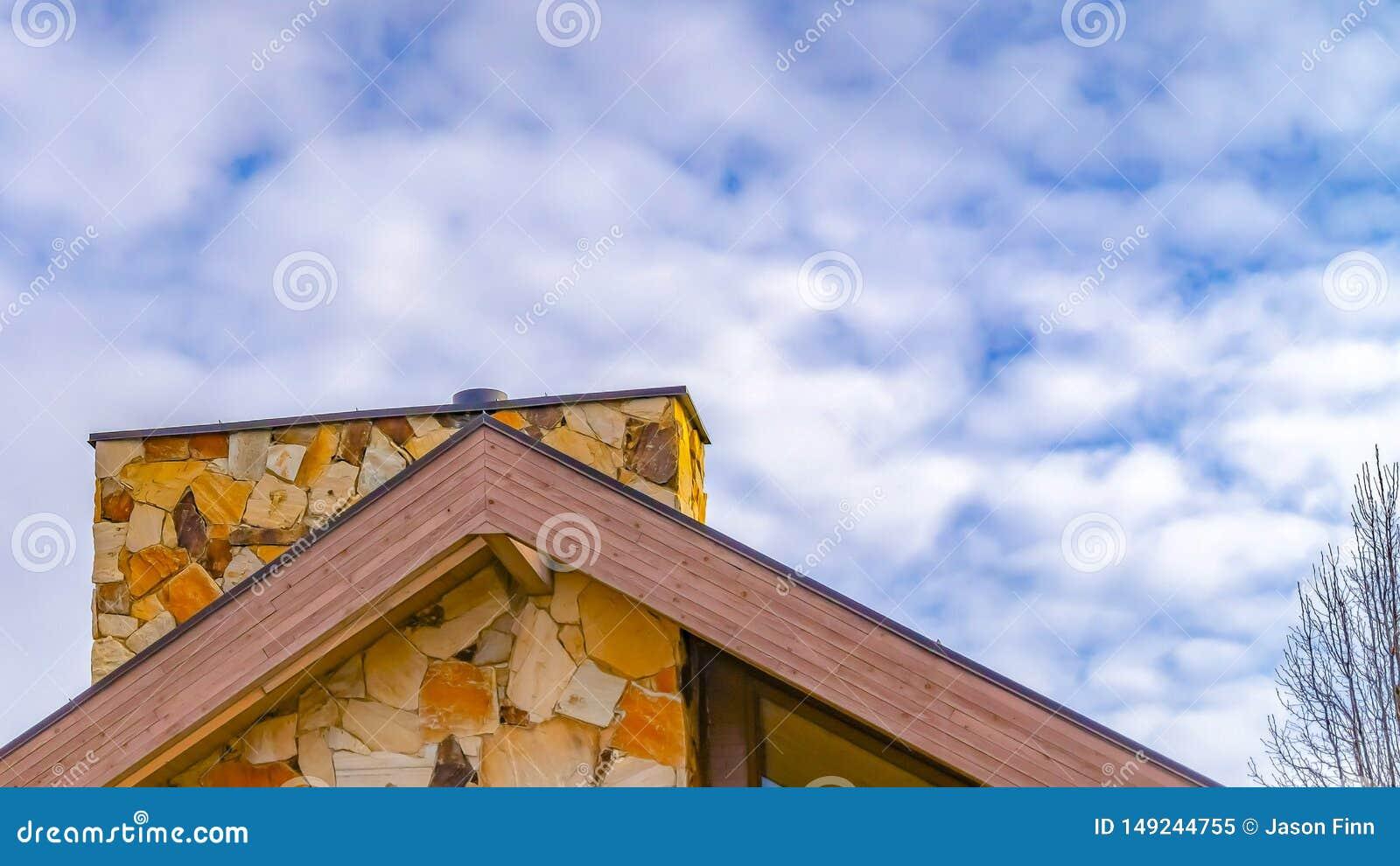 Dichte omhooggaand van het panoramakader van het dak van een huis tegen bomen en hemel met donzige wolken