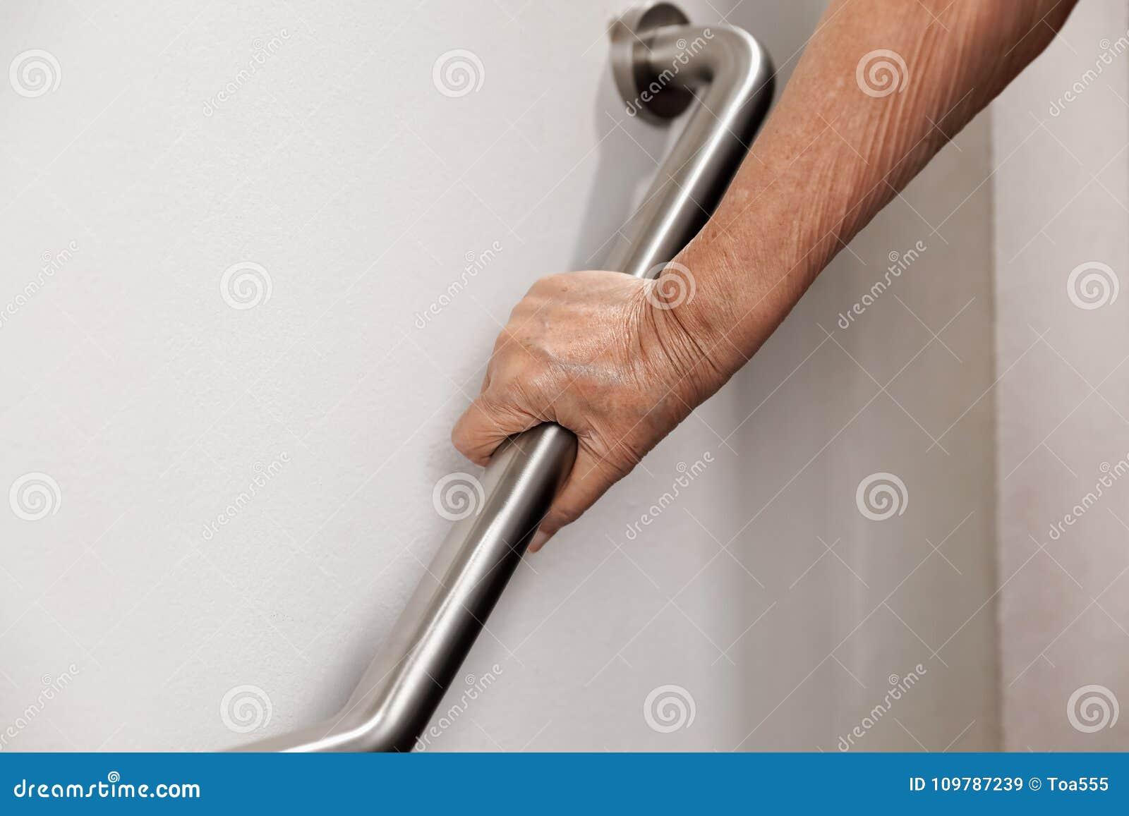 Die ältere Frau, die an Handlauf zur Sicherheit hält, tritt