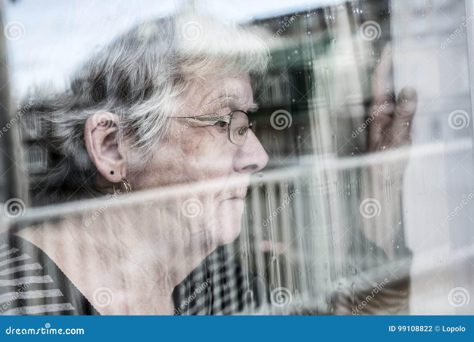 Die ältere Frau, die heraus durch ein Fenster wie schaut, drücken nieder