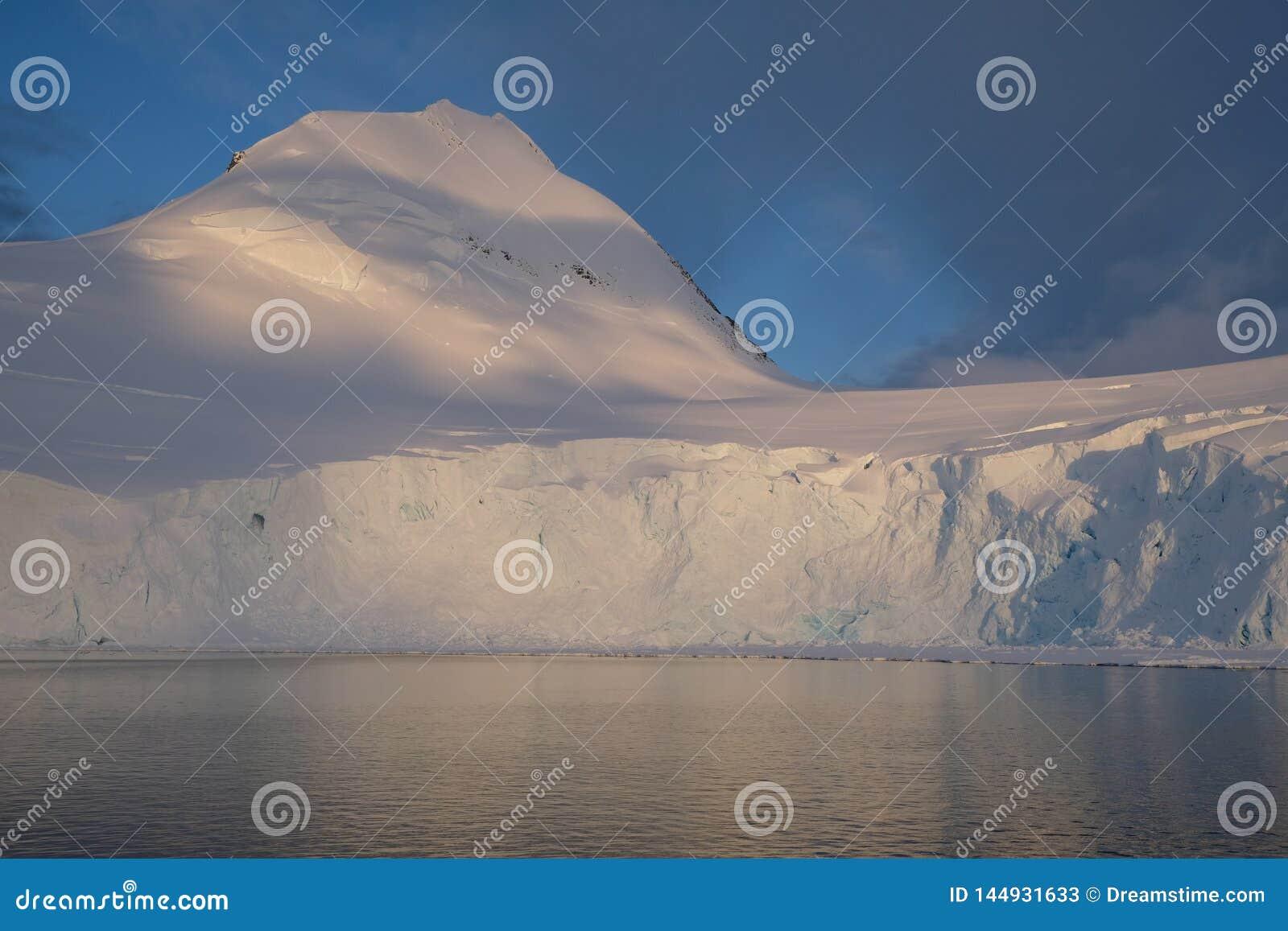 Die Antarktis-Ruhemitternachtssonnenuntergang auf schneebedecktem Berg