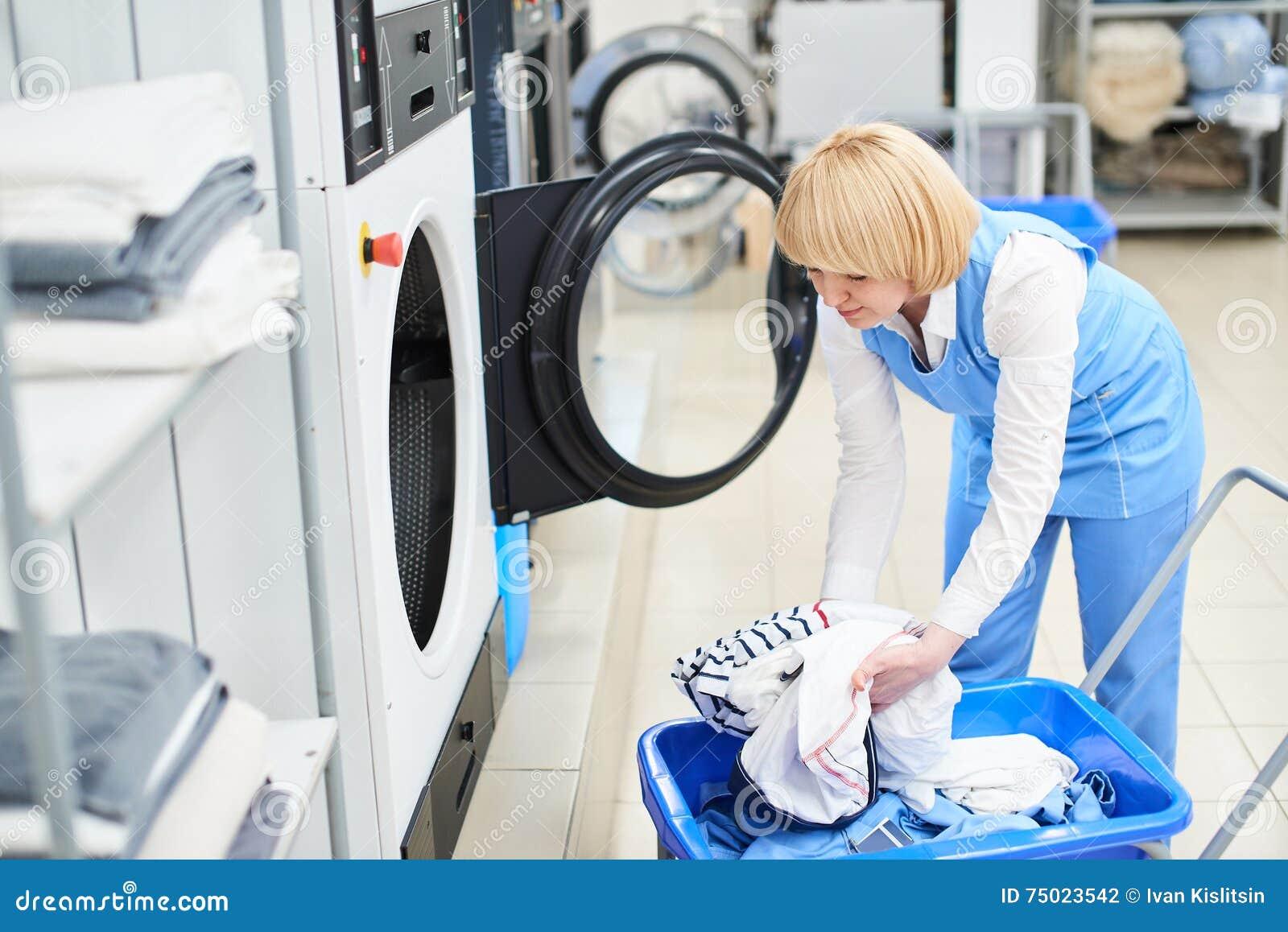 Die Arbeitskraft lädt die Wäschereikleidung in die Waschmaschine