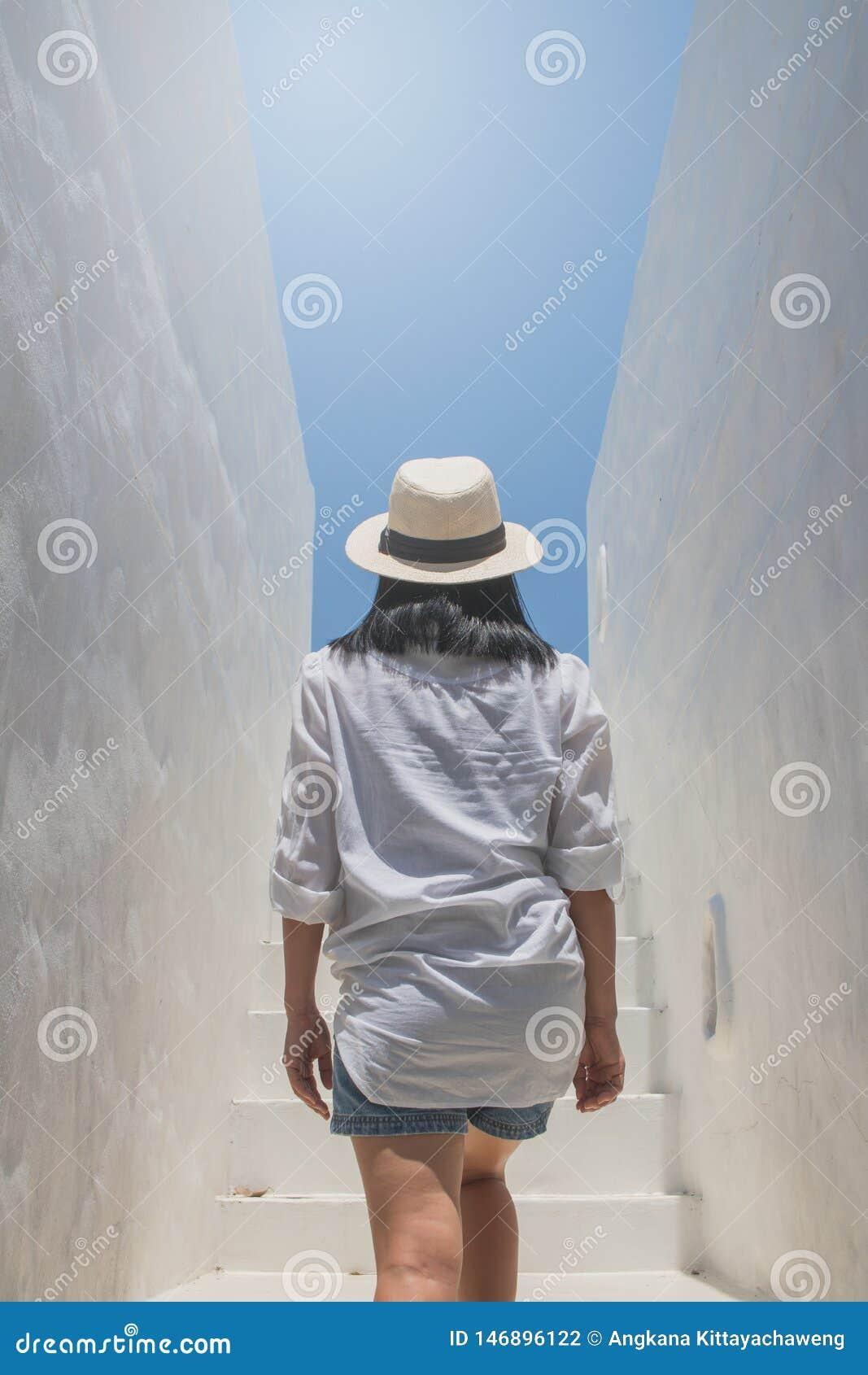 Die Asiatin tragen weißen Hemd- und Webarthut gehend oben auf konkrete Treppe