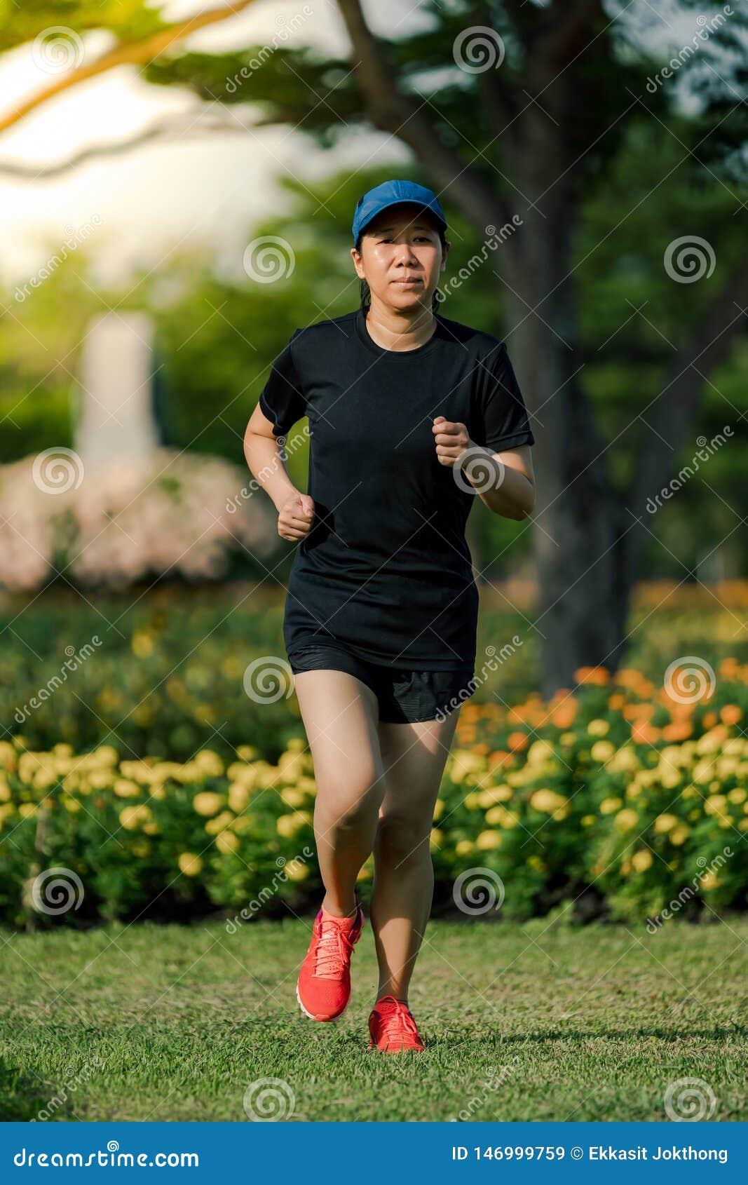 Die asiatische Frau von mittlerem Alter, die ein schwarzes Kleid, den blauen Hut, laufend in den Park tr?gt, erhalten das Sonnenl