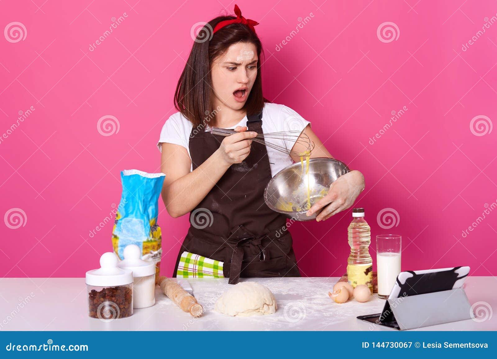 Die Atelieraufnahme der Frau Eier in der K?che wischend, hat erstaunt, dass Gesichtsausdruck, selbst gemachtes Geb?ck machend, ba