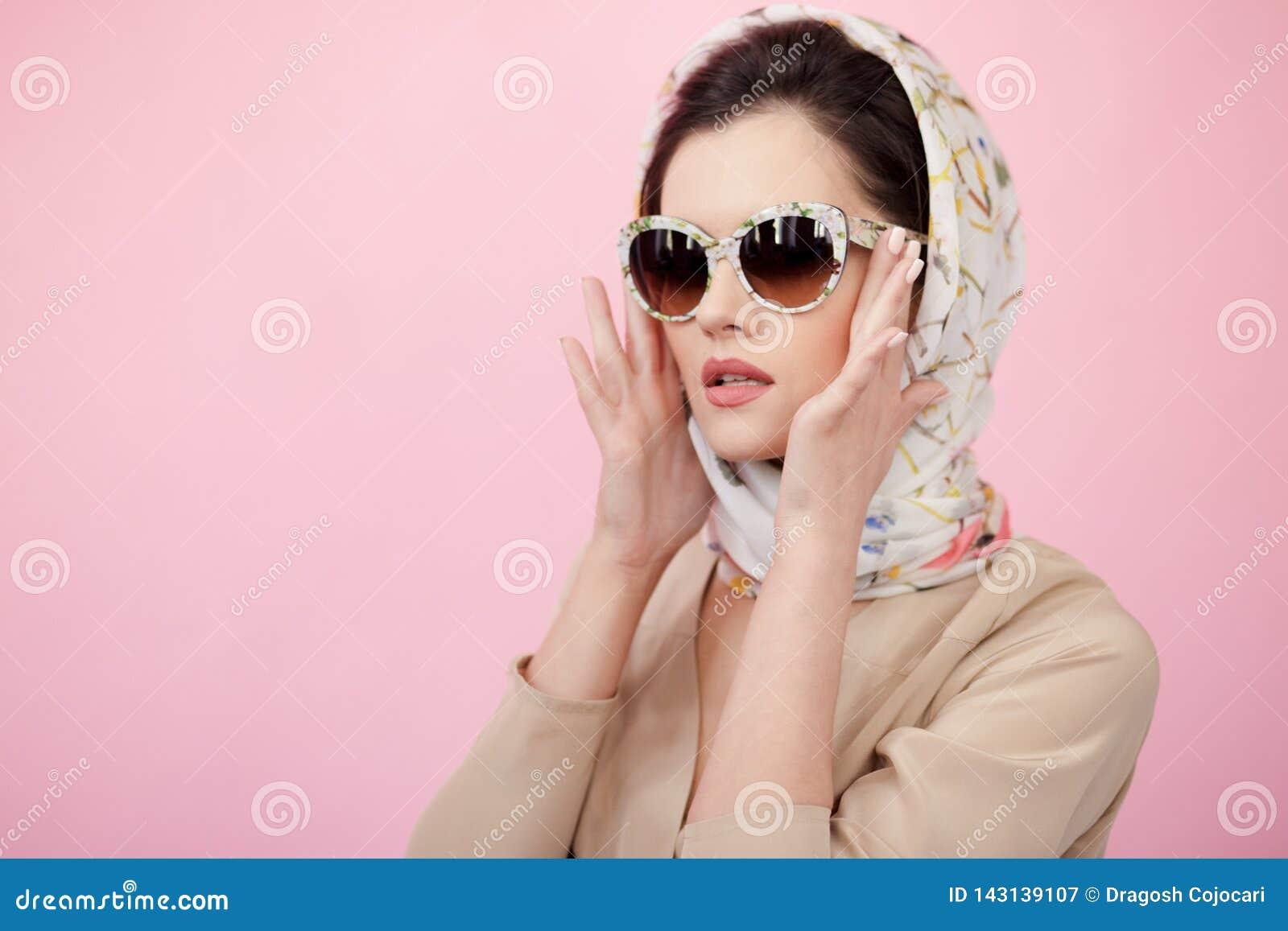 Die attraktive junge Frau, die im Seidenschal trägt, berührt seine Sonnenbrille mit seinen Händen, lokalisiert auf rosa Hintergru