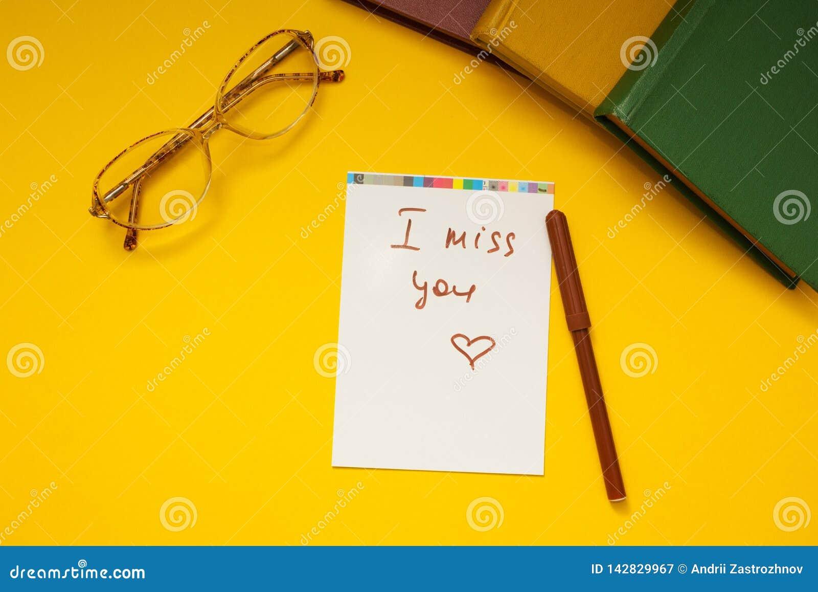 Die Aufschrift 'du fehlst mir 'auf einem gelben Hintergrund, Gläsern und Büchern zusammen