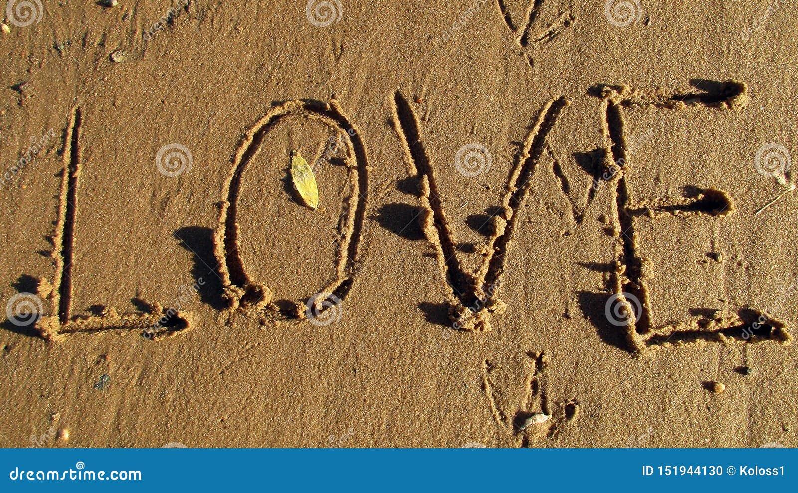 Die Aufschrift auf dem nass Sand Die Wort Liebe
