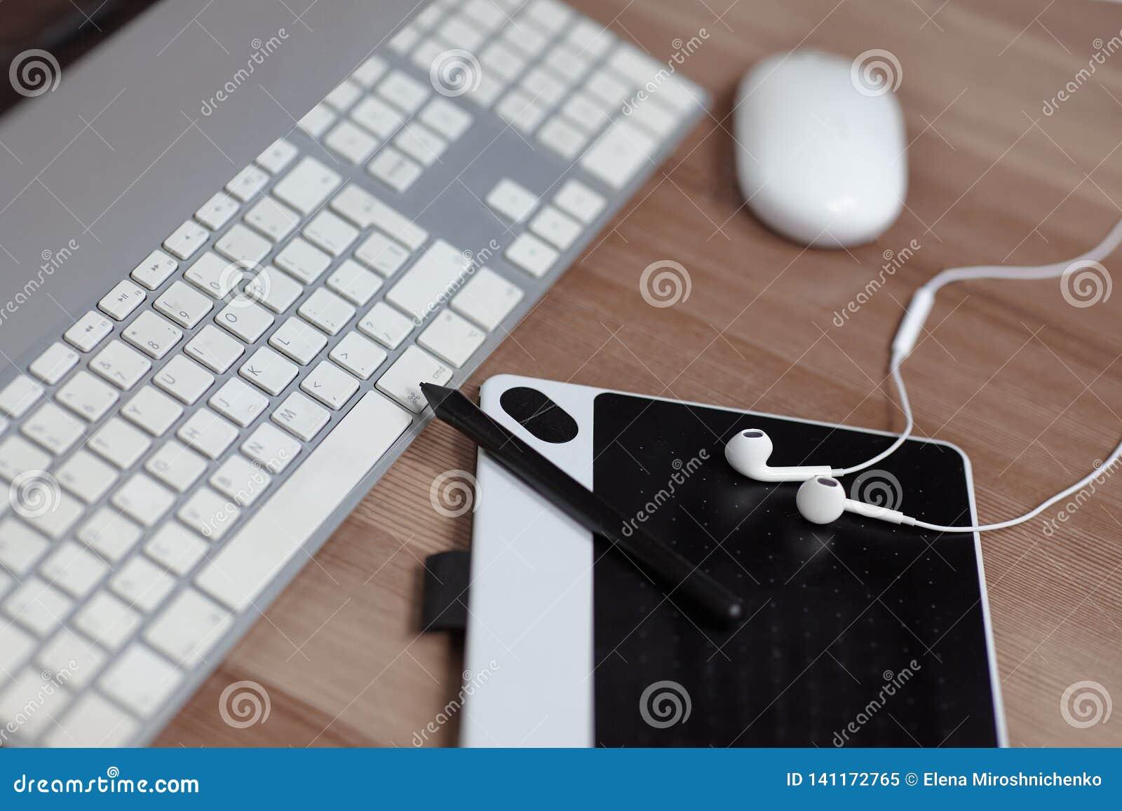 Die Ausrüstung des Fotografen oder des grafic Designercomputers, der Maus, der grafic Tablette, des Griffels und der Kopfhörer Ar