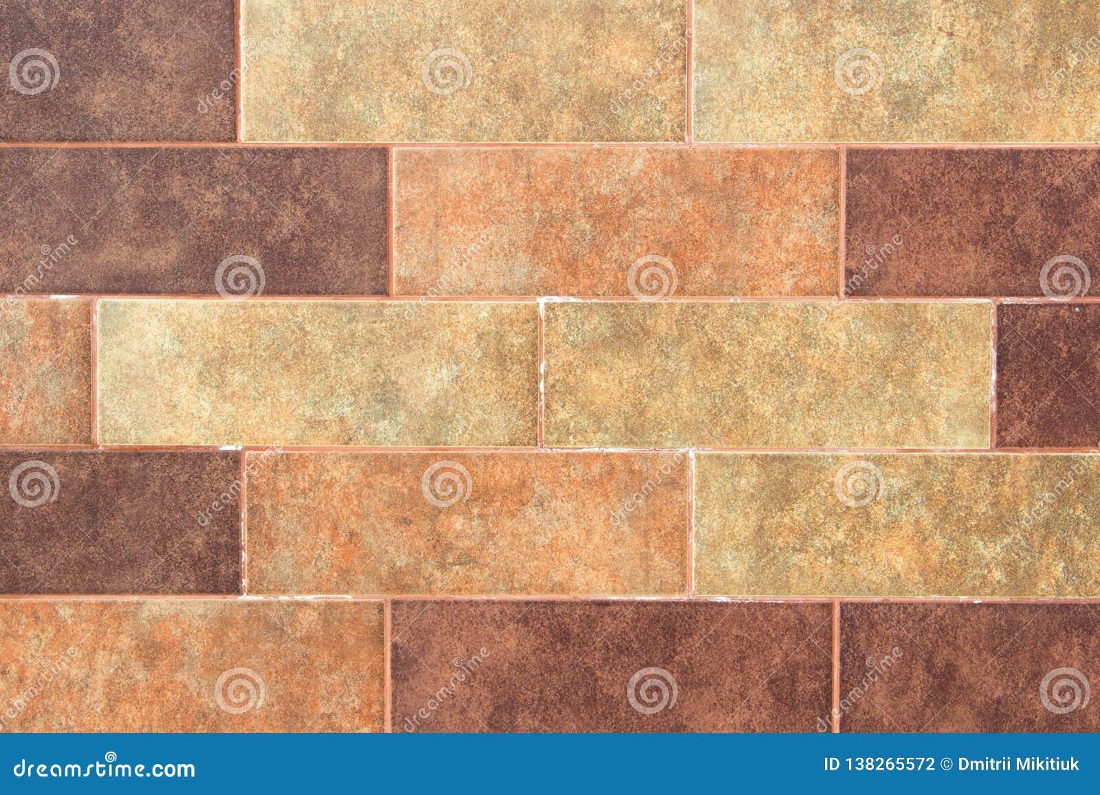 Die Beschaffenheit einer Backsteinmauer der dekorativen mehrfarbigen rechteckigen Ziegelsteine mit Geräuschen, Kratzer