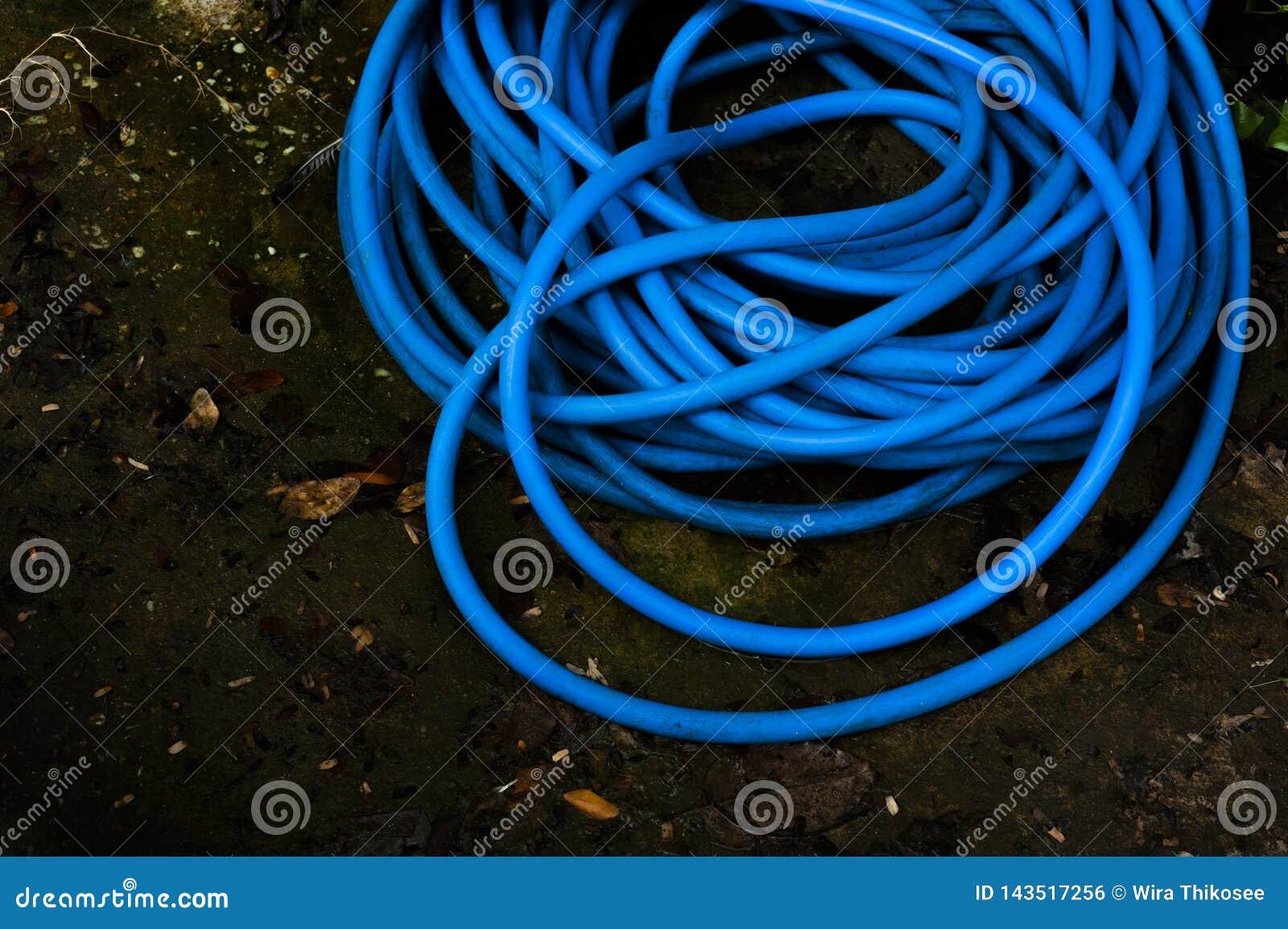 Die blaue Plastikwasserleitung gesetzt auf nass Boden