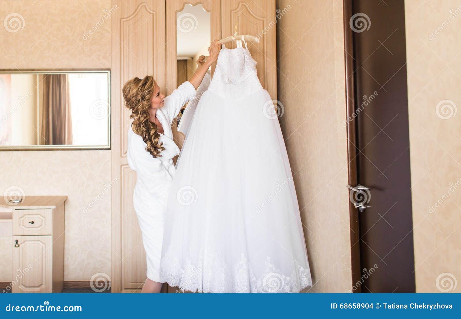 Die Braut Im Weißen Bademantel Hochzeitskleid Und -schuhe Stockfoto ...