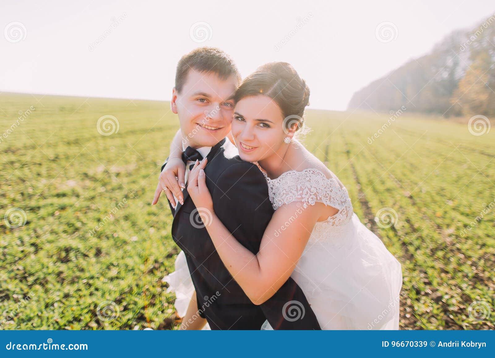 Die Braut umarmt den Bräutigam zurück auf dem grünen Gebiet