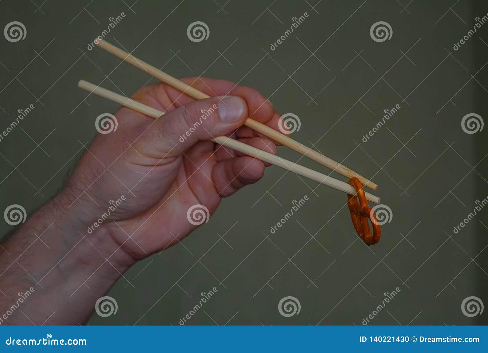 Die chinesischen Essstäbchen in einer Hand