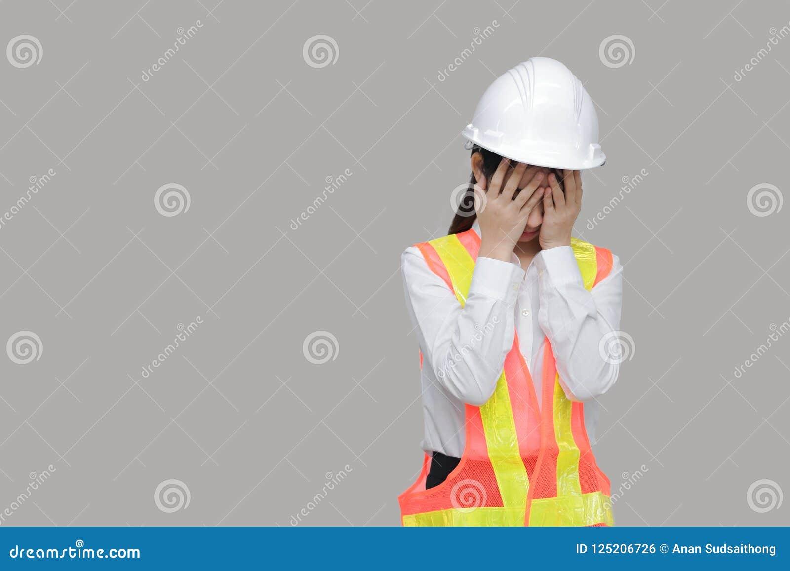 Die deprimierte betonte junge asiatische Arbeitskraft mit den Händen auf Gesicht schreiend auf Grau lokalisierte Hintergrund
