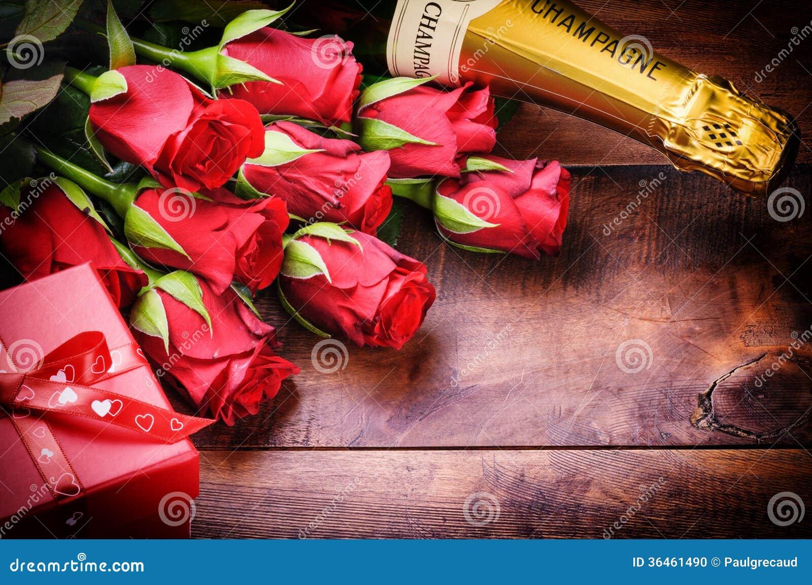 Die Einstellung des Valentinsgrußes mit roten Rosen, Champagner und Geschenk