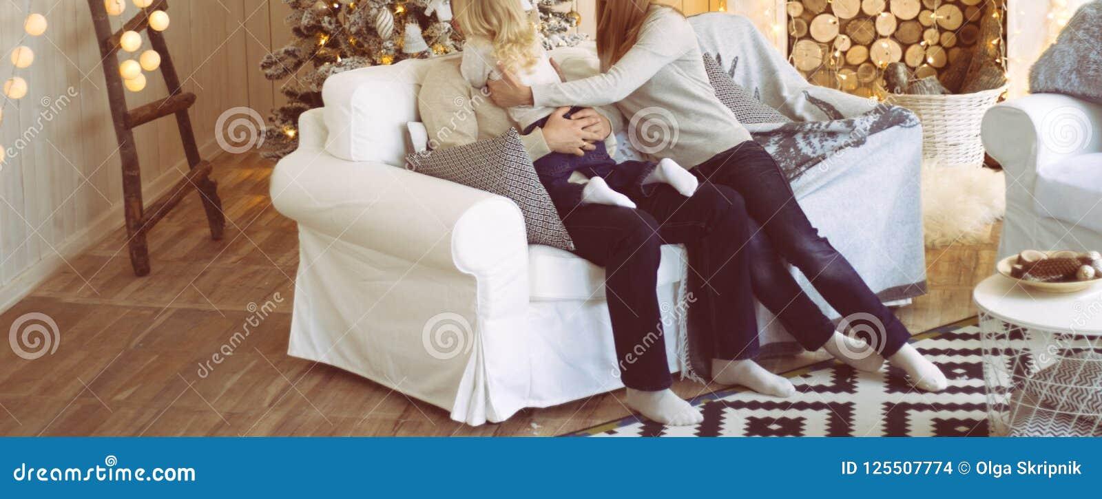 Die Familie nahe dem Kamin und dem Weihnachtsbaum sitzt auf der Couch, das Mädchen erreicht heraus zu ihrem Vater, umarmen ihn Co