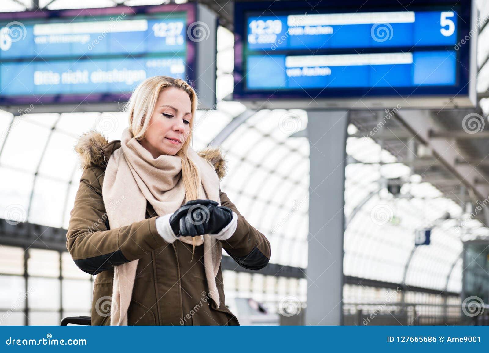 Die Frau, die Armbanduhr in der Bahnstation als ihr Zug betrachtet, hat eine Verzögerung