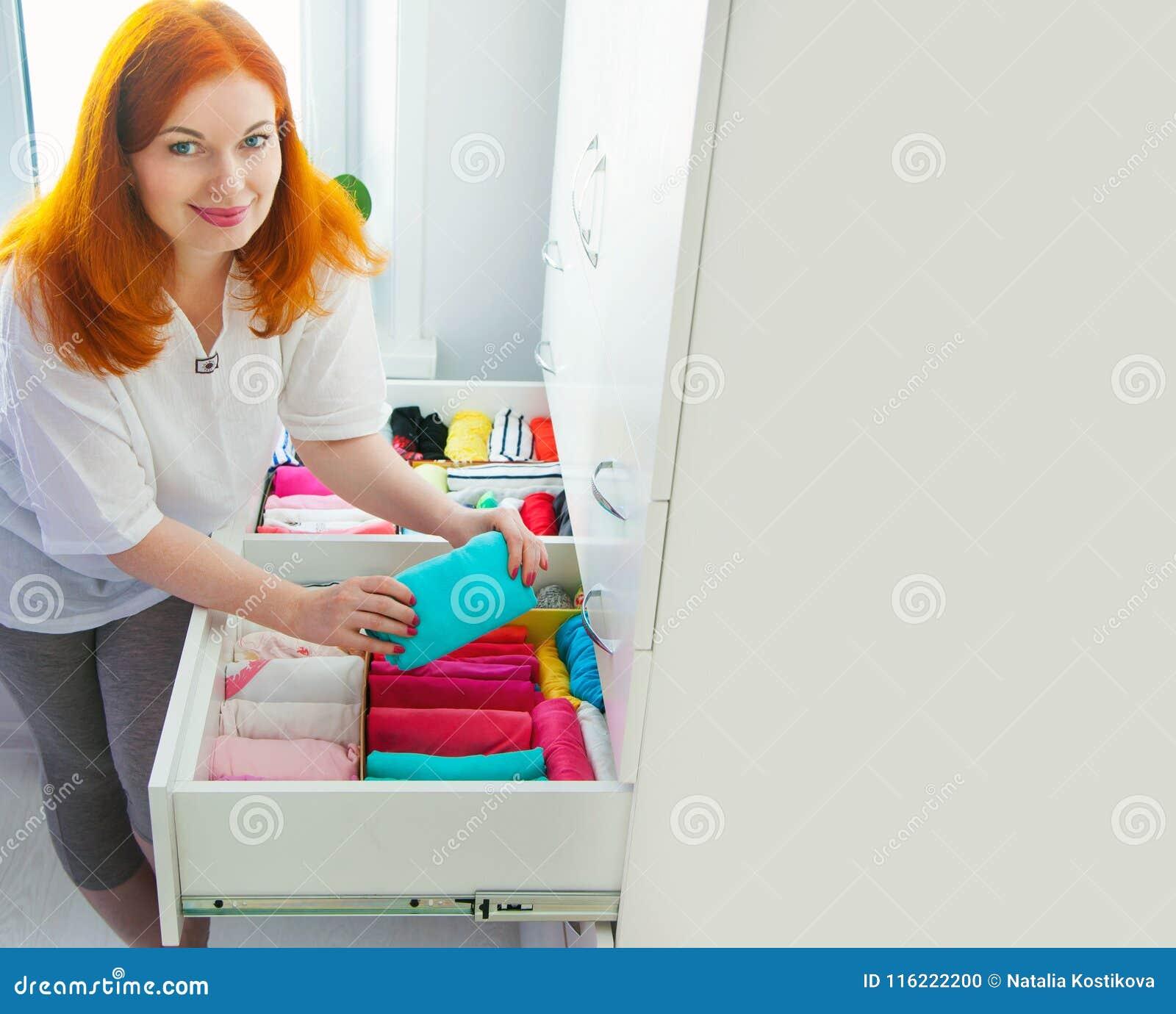 Die Frau faltet T-Shirts im Fach Eine Frau räumt Th auf