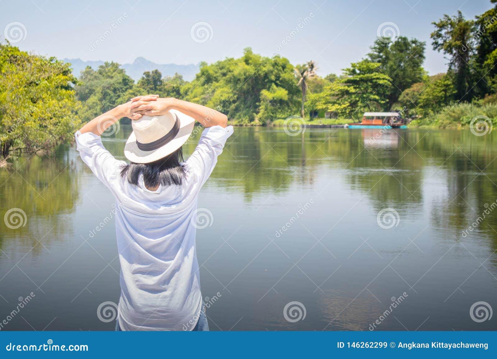 Die Frau, die vorwärts zum Fluss mit schaut, ihre Hände auf Kopf und sie zu setzen, lässt Gefühl sich entspannen und Glück