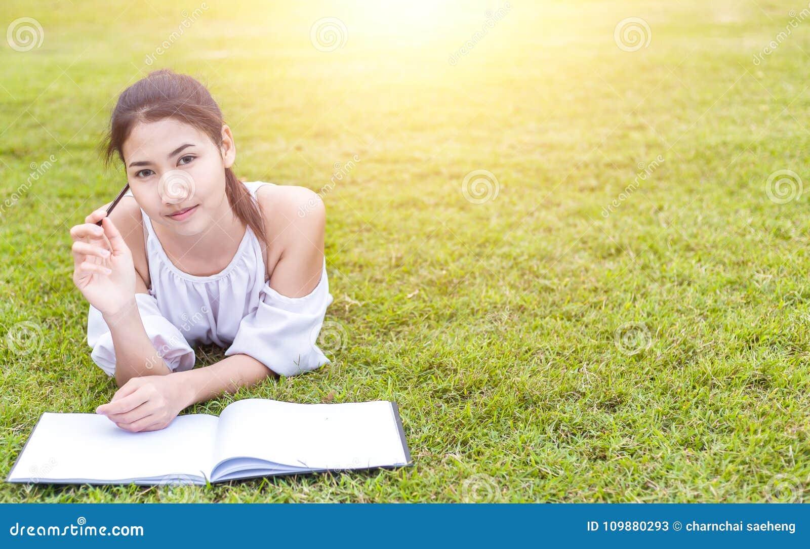 Die Frauen ist auf dem Gras und schön Sie denkt, dass… Sie Job finden sollen, was! das Buch ist auf dem Gras sie trägt weißes Kle