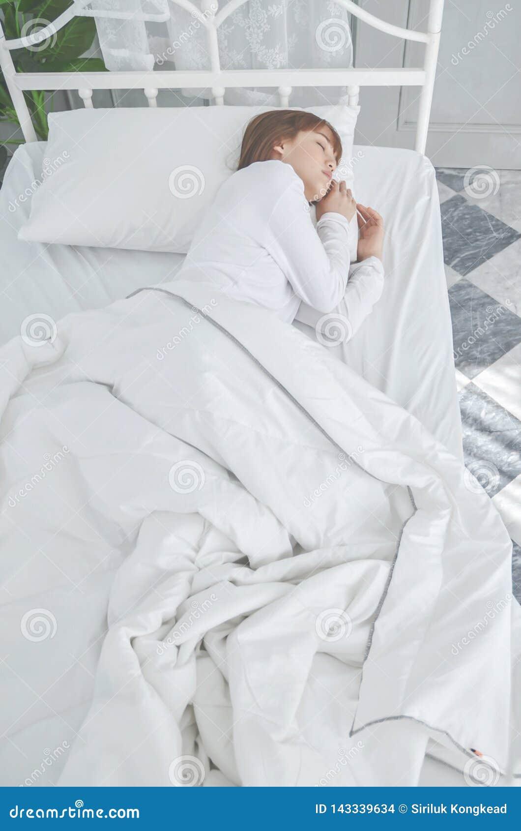 Die Frauen, die wei?e Pyjamas tragen, stehen auf der Matratze still