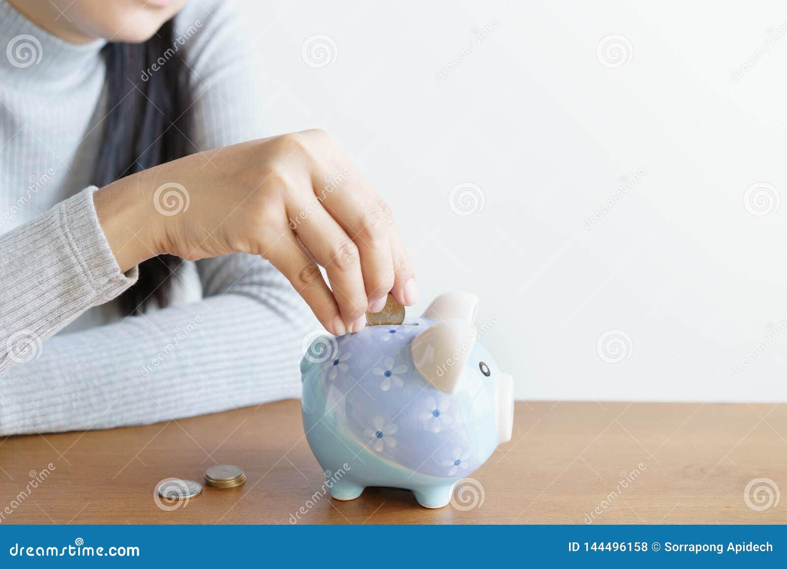 Die Frauenhände, welche die piggy Münzen setzen, sparen Geld für Investition Konzept des Einsparunggeldes