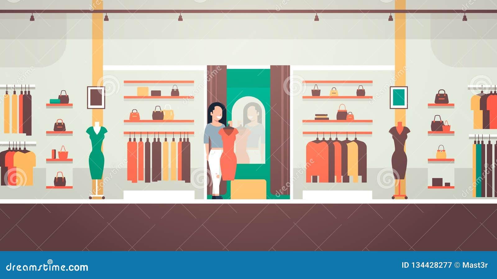 Die Geschäftsfrau, die auf der neues Kleidereleganten Frau betrachtet Spiegelmode-Geschäftsfrauenkleider versucht, vermarkten das