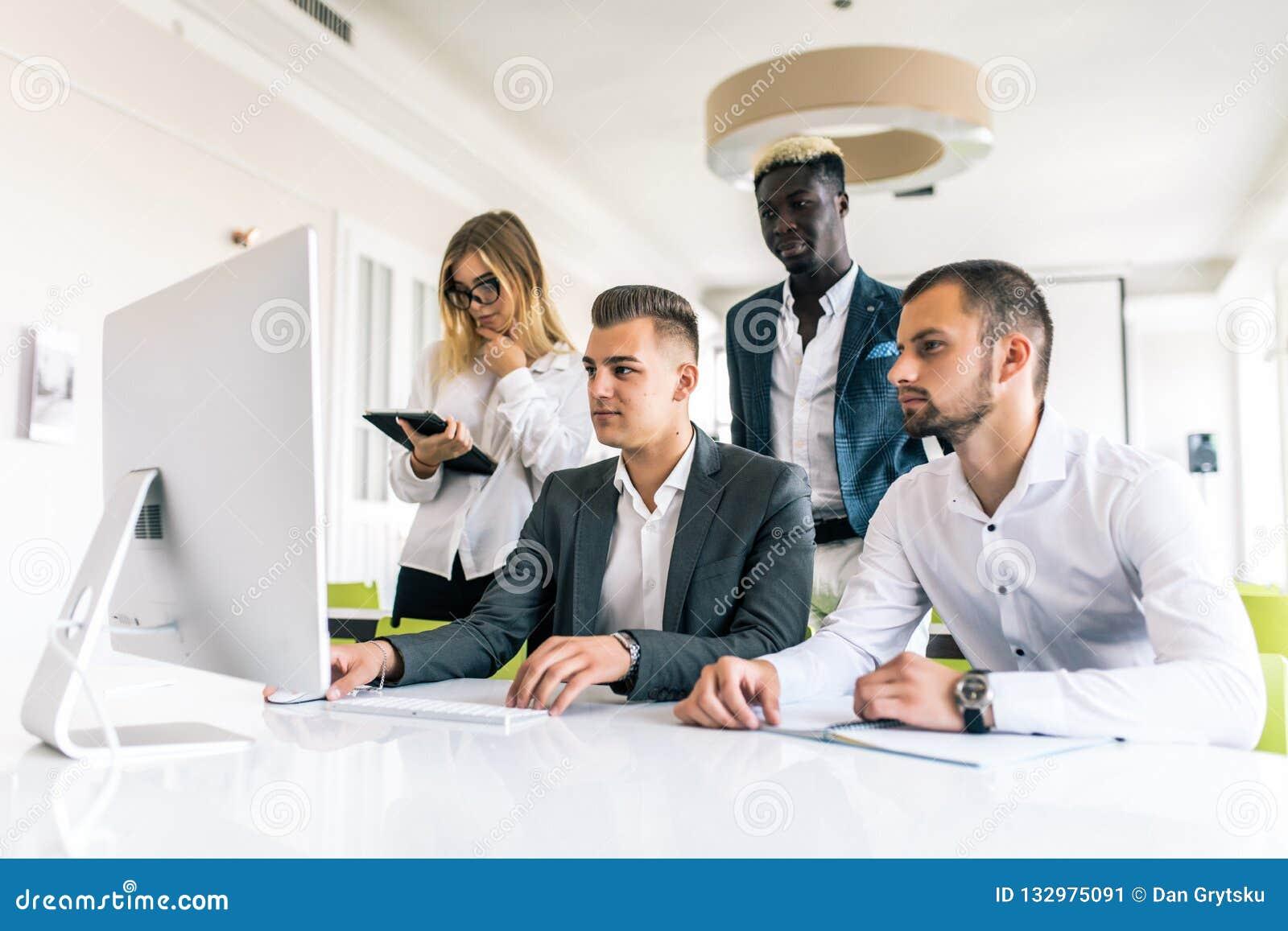 Die Geschäftsleute, die Team zeigen, arbeiten beim Arbeiten in der Chefetage im Büroinnenraum Leute, die einem ihres Kollegen hel