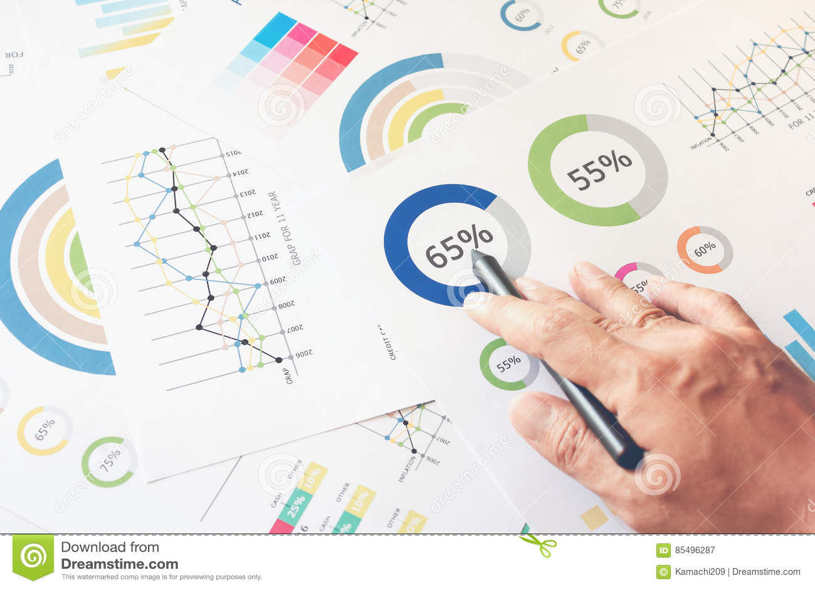 Die Geschäftsmannhand, die an hölzernem Schreibtisch im Büro und dort arbeitet, sind viele Dokumente, Diagramme Kann Finanzartike