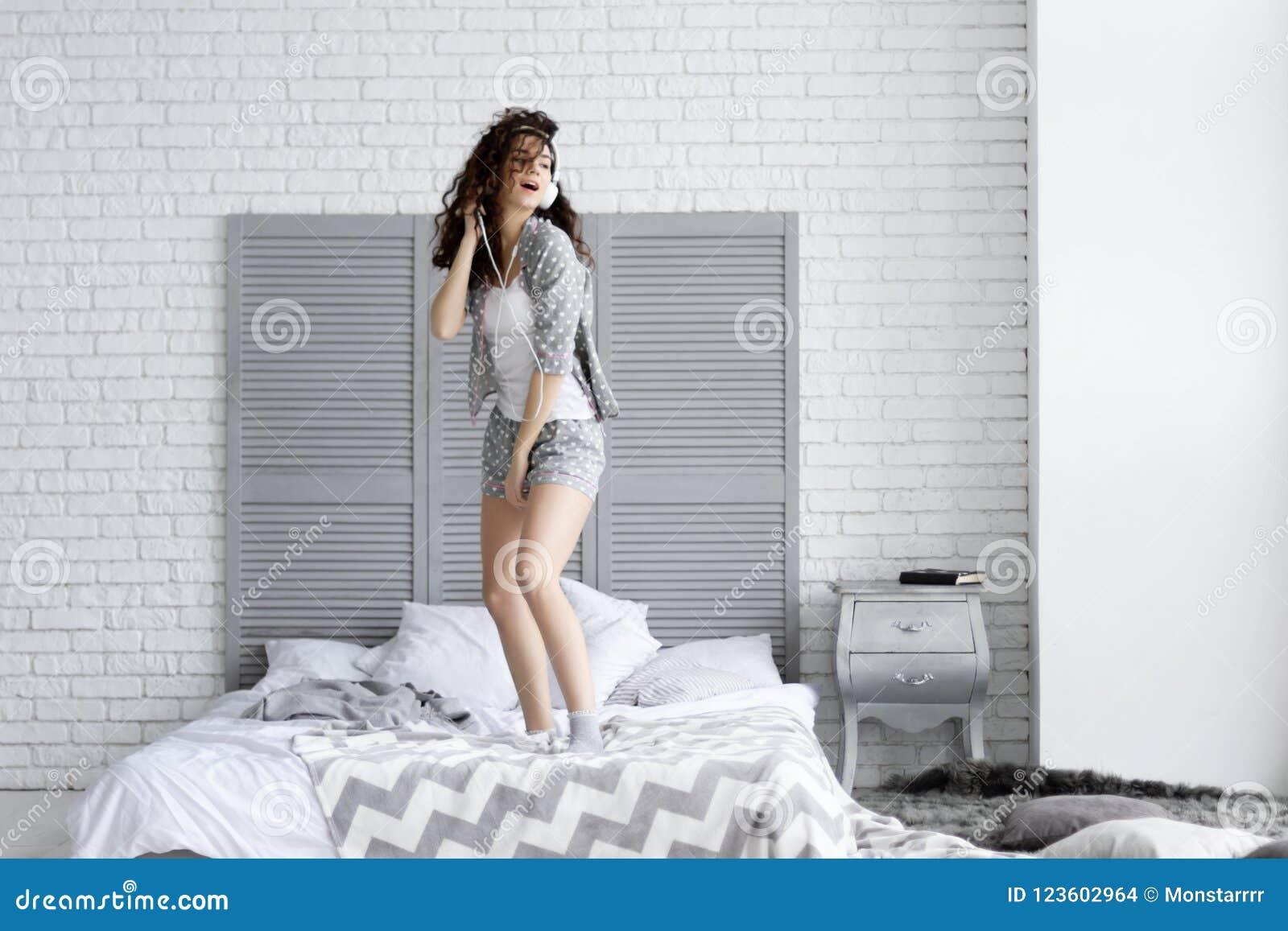 Die glückliche Brunettefrau trägt graue Pyjamakopfhörer hörend auf Musiktanzen