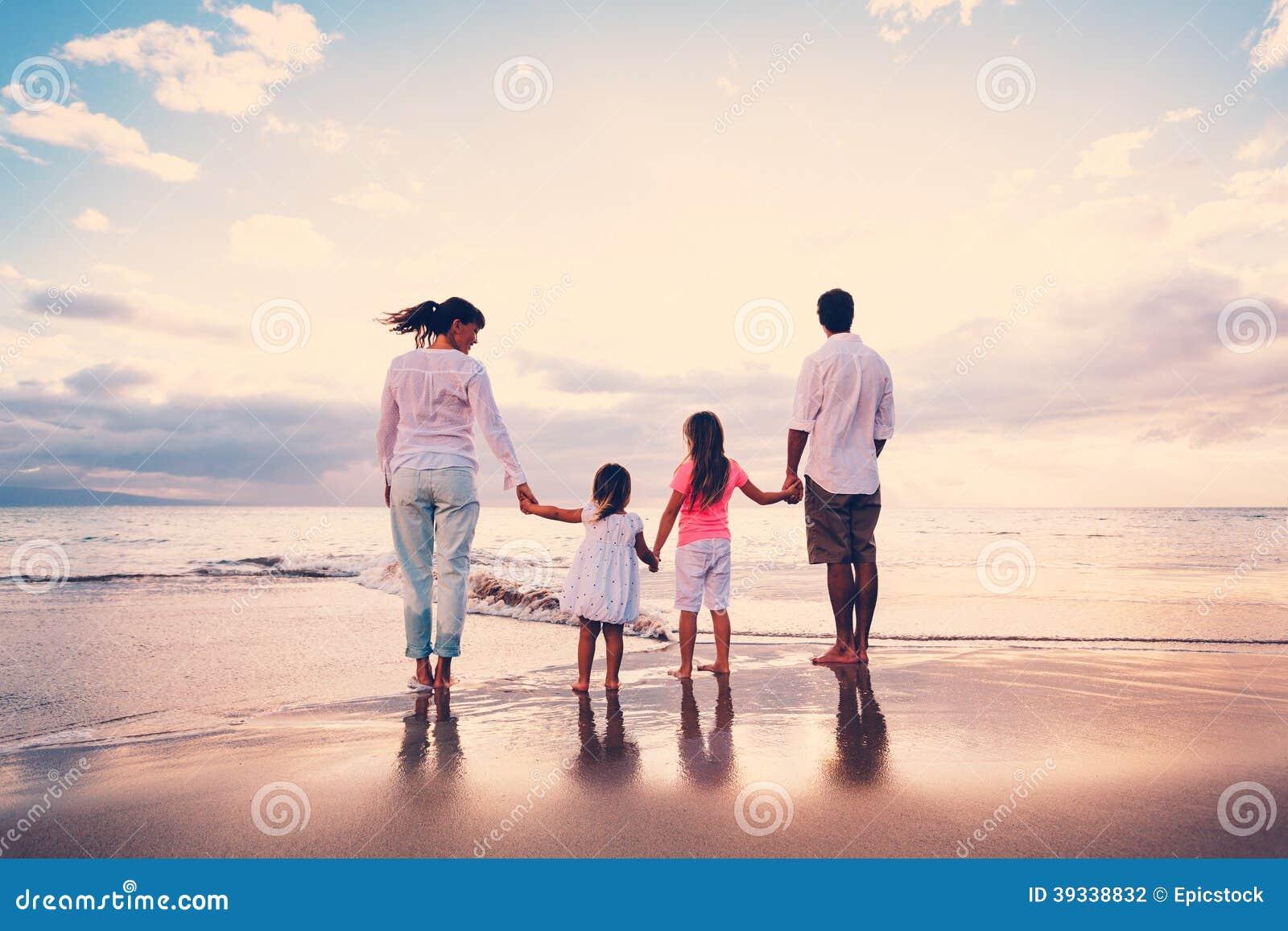 Die glückliche Familie haben Spaß gehend auf Strand bei Sonnenuntergang
