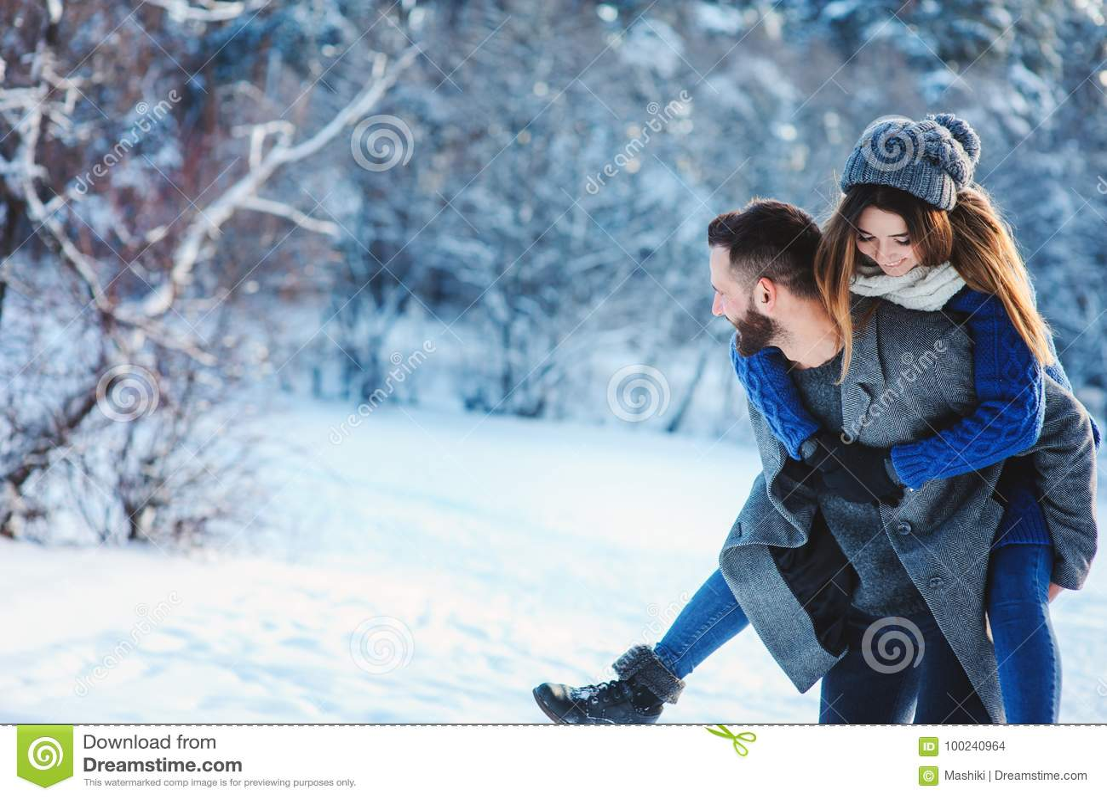 Die glücklichen liebevollen Paare, die in den Wald des verschneiten Winters, Weihnachten aufwendend gehen, machen zusammen Urlaub