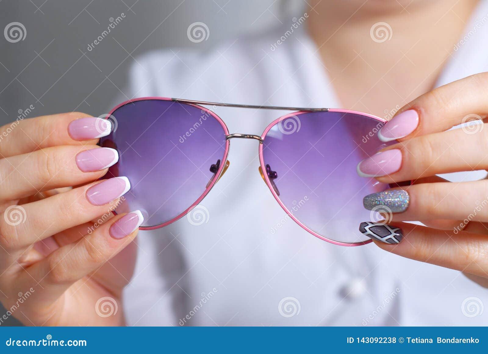 Die Hände der Frau mit einer schönen Maniküre überprüft Sonnenbrille