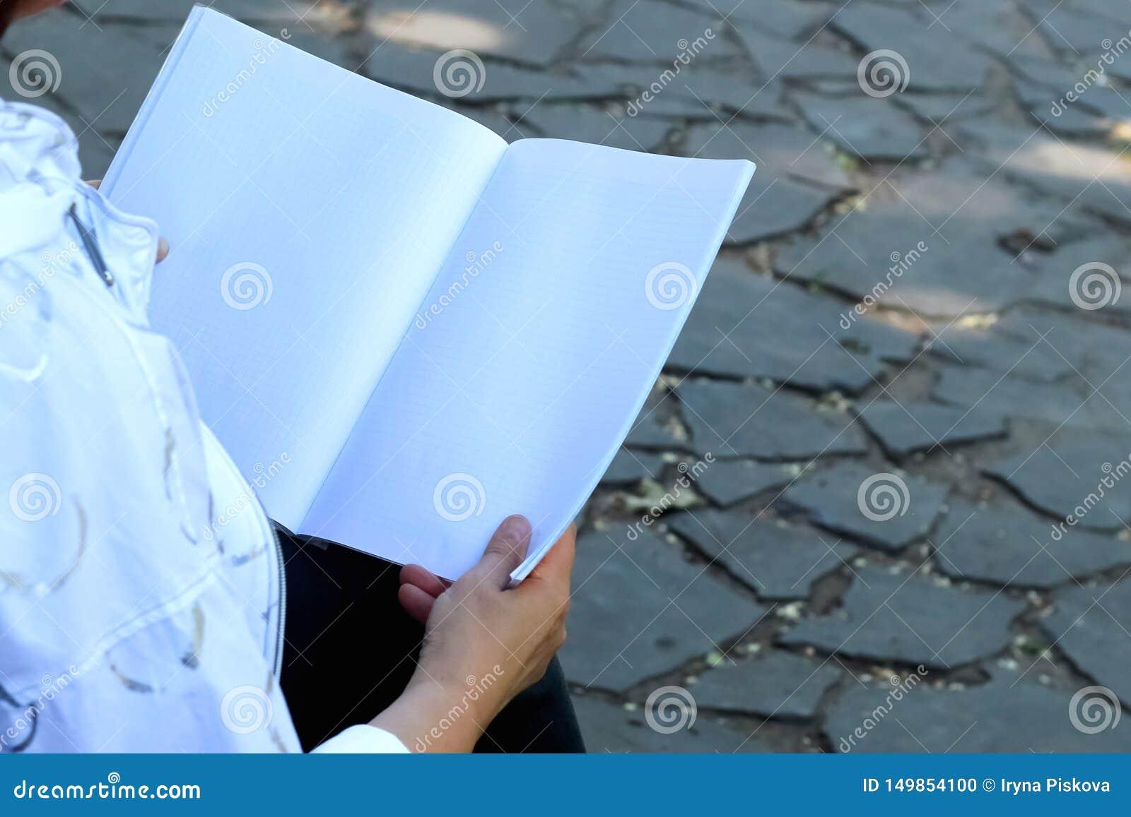 Die Hände der Frau, die Notizbuch halten